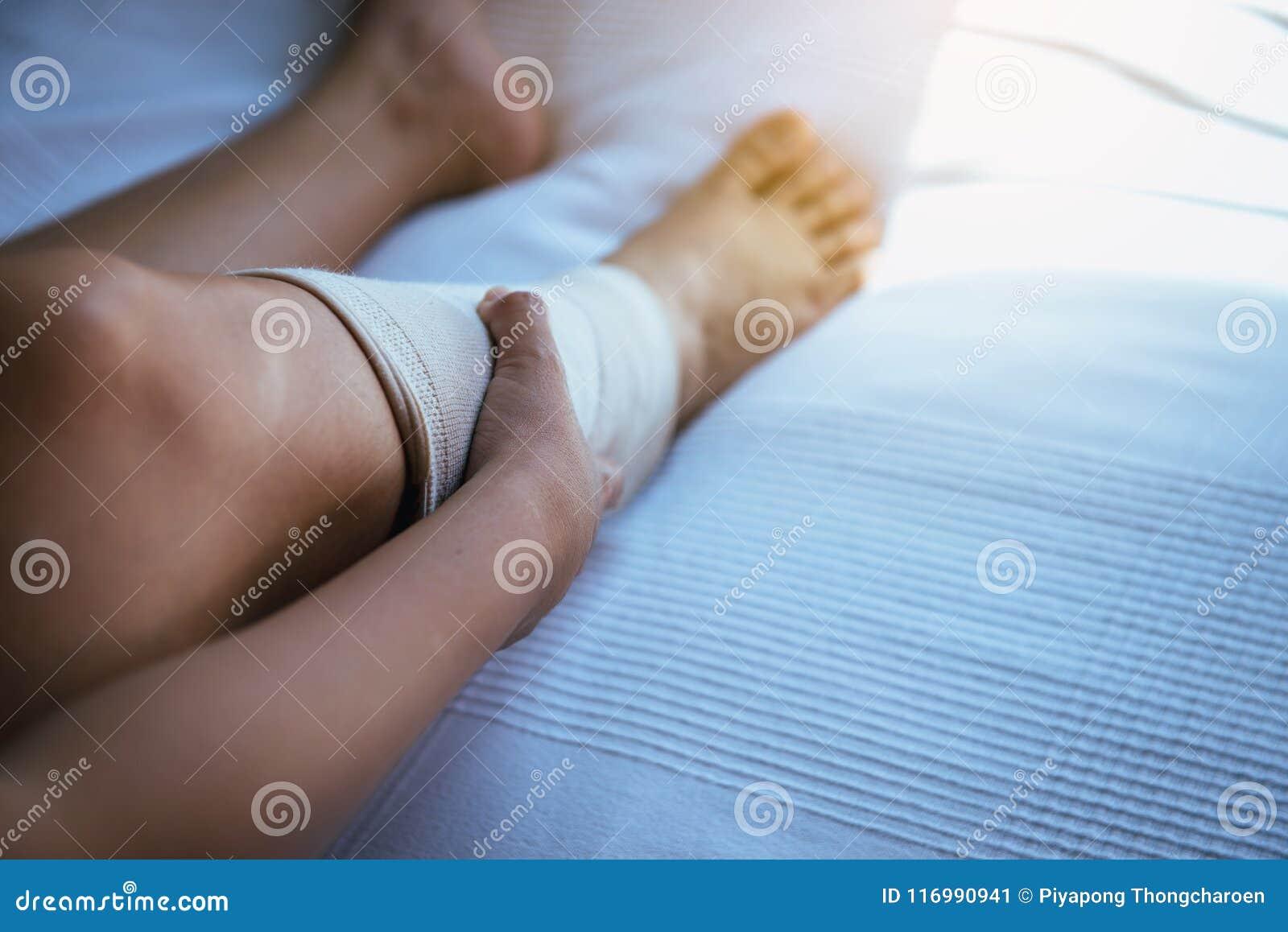 Mulher que usa a atadura elástica sobre posta com os pés que têm a dor do joelho ou de pé
