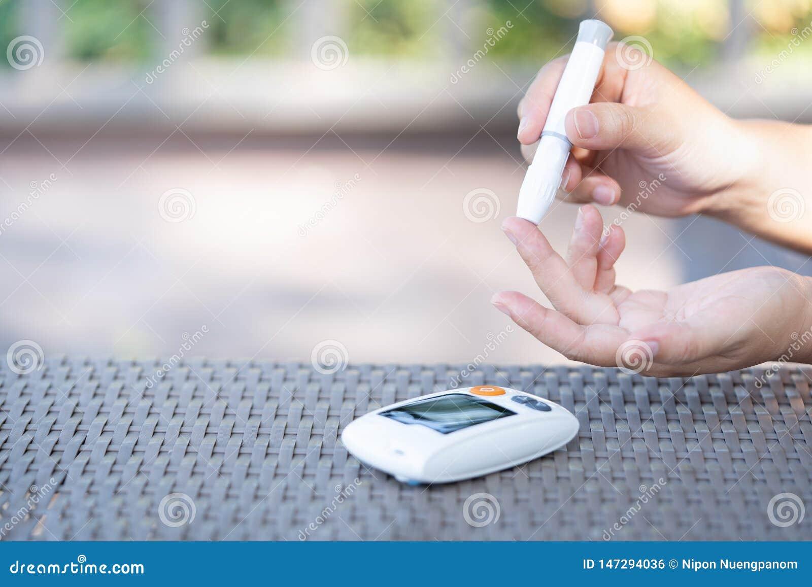 Mulher que usa a lanceta no dedo para verificar o nível do açúcar no sangue