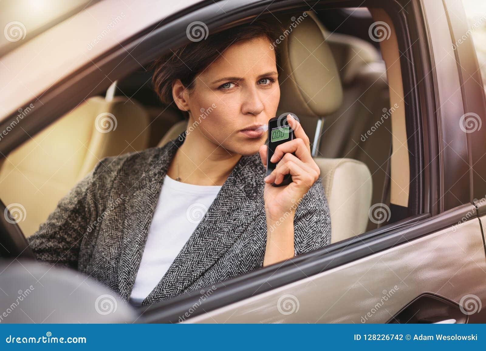 Mulher que usa o analisador do álcool da respiração no carro