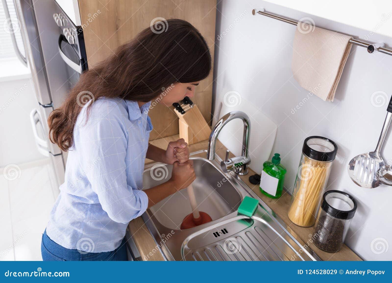 Mulher que usa o atuador na banca da cozinha obstruída