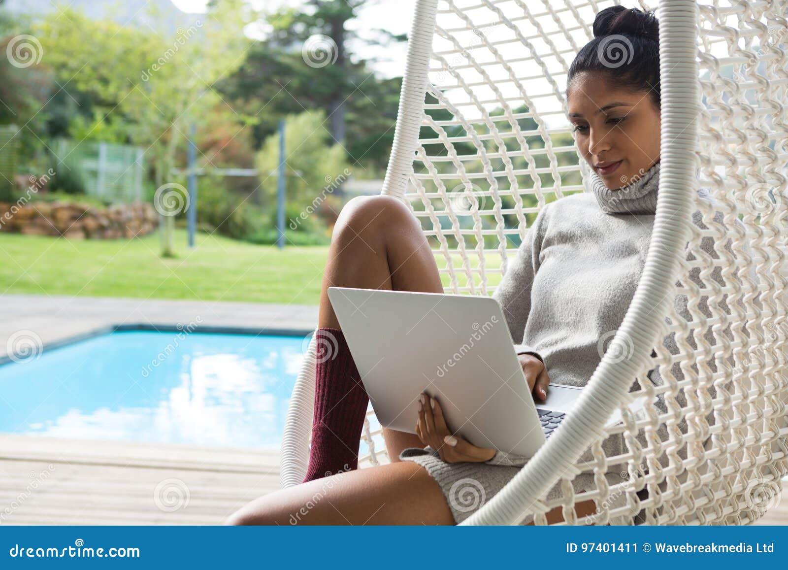 Mulher que usa o portátil ao descansar no balanço