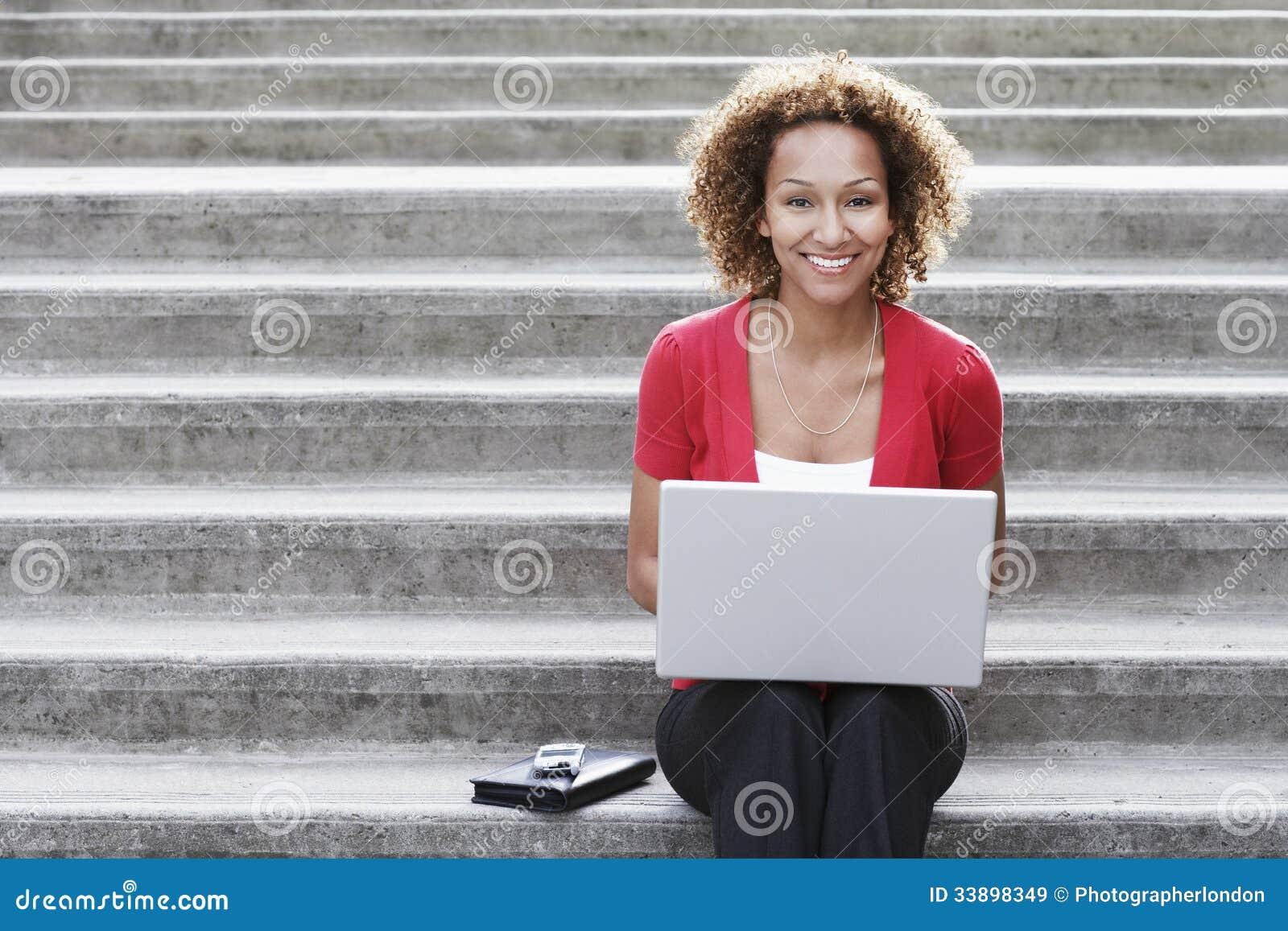 Mulher que usa o portátil em etapas fora