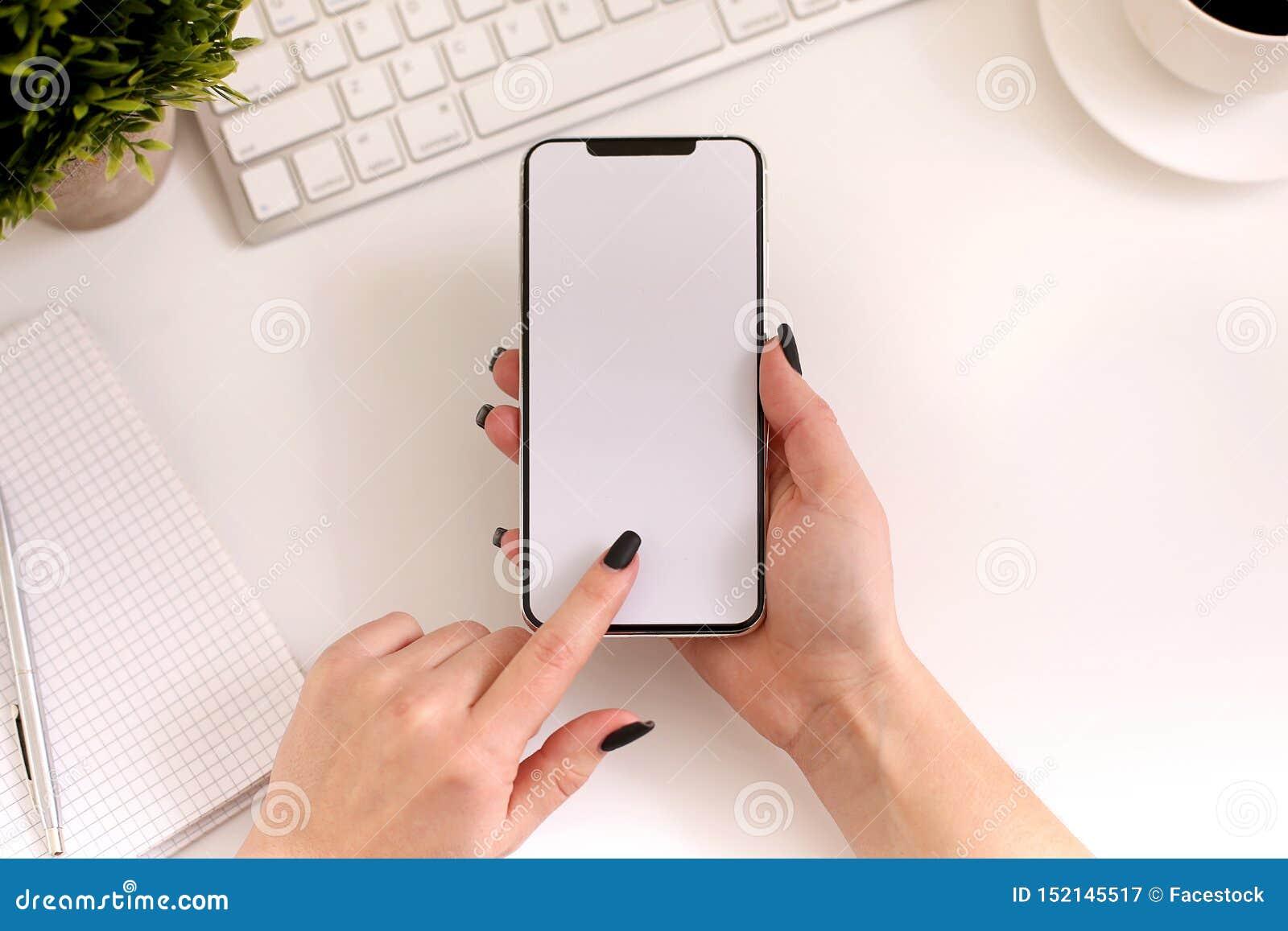 Mulher que usa o smartphone no trabalho Tela vazia branca, vista superior