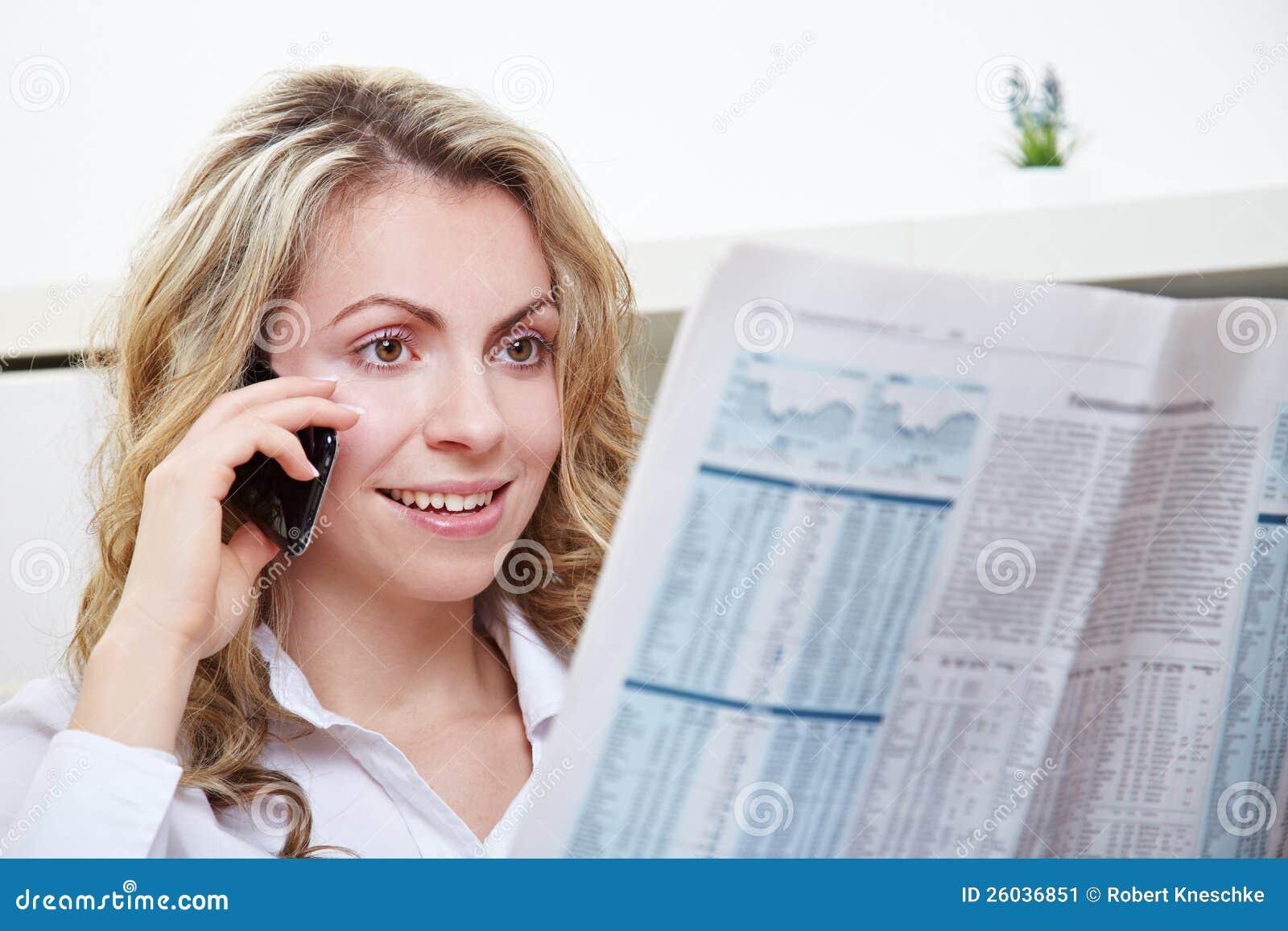 Mulher que usa o telefone ao ler