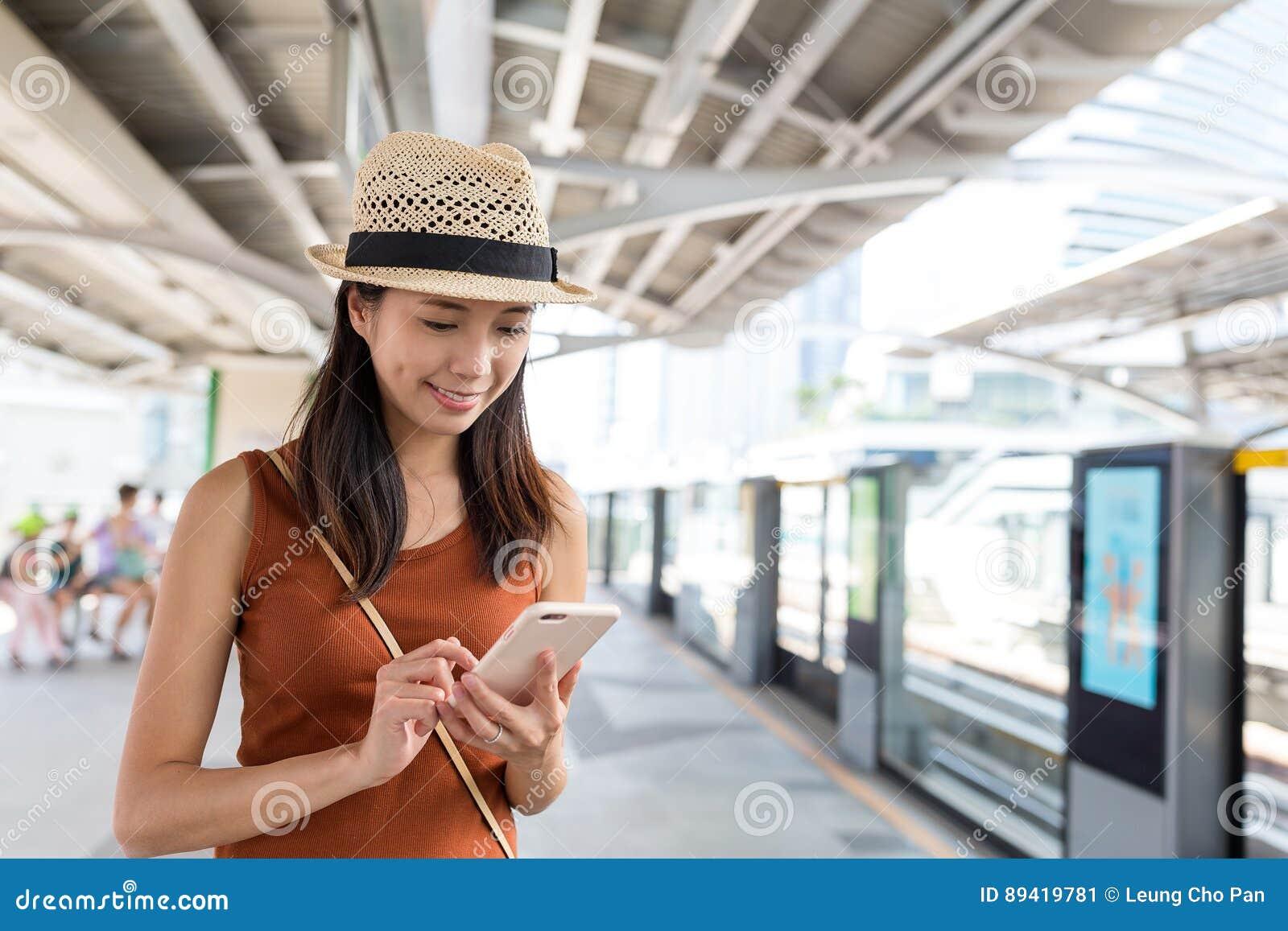 Mulher que usa o telefone celular na cidade de Banguecoque