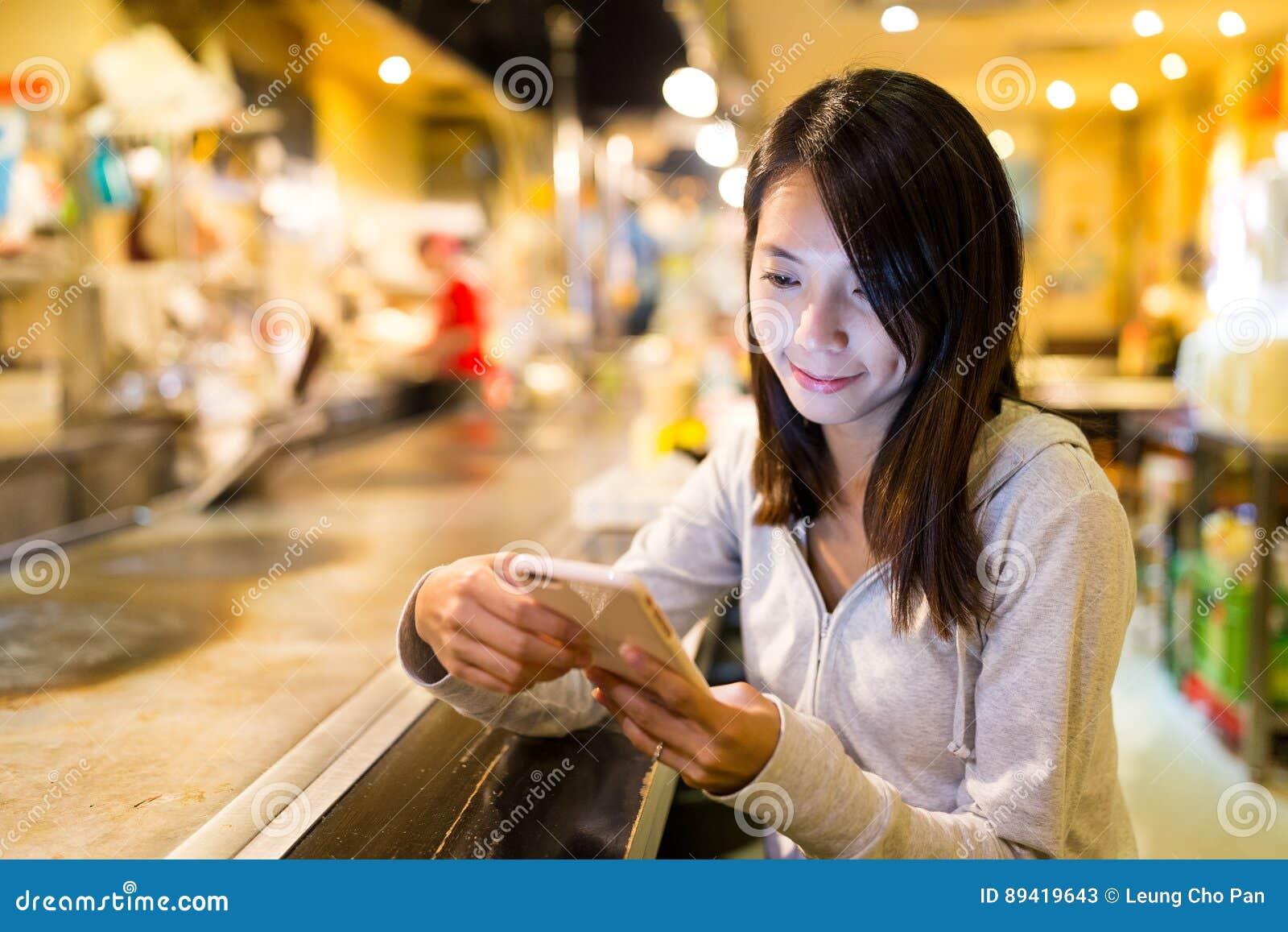Mulher que usa o telefone celular no restaurante japonês