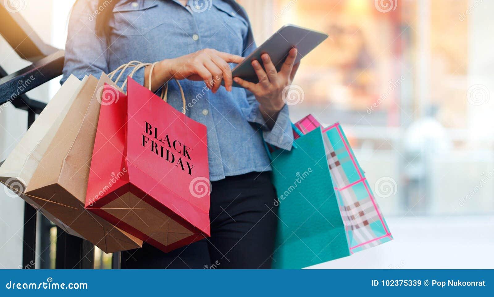 Mulher que usa a tabuleta e guardando o saco de compras de Black Friday