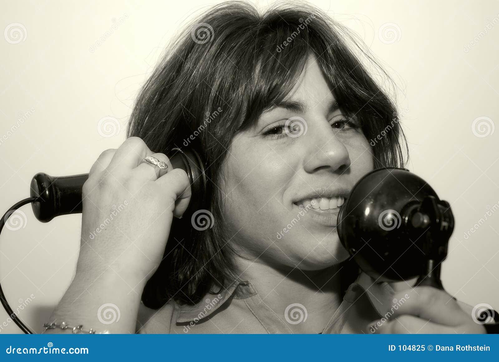 Mulher que usa um telefone do vintage