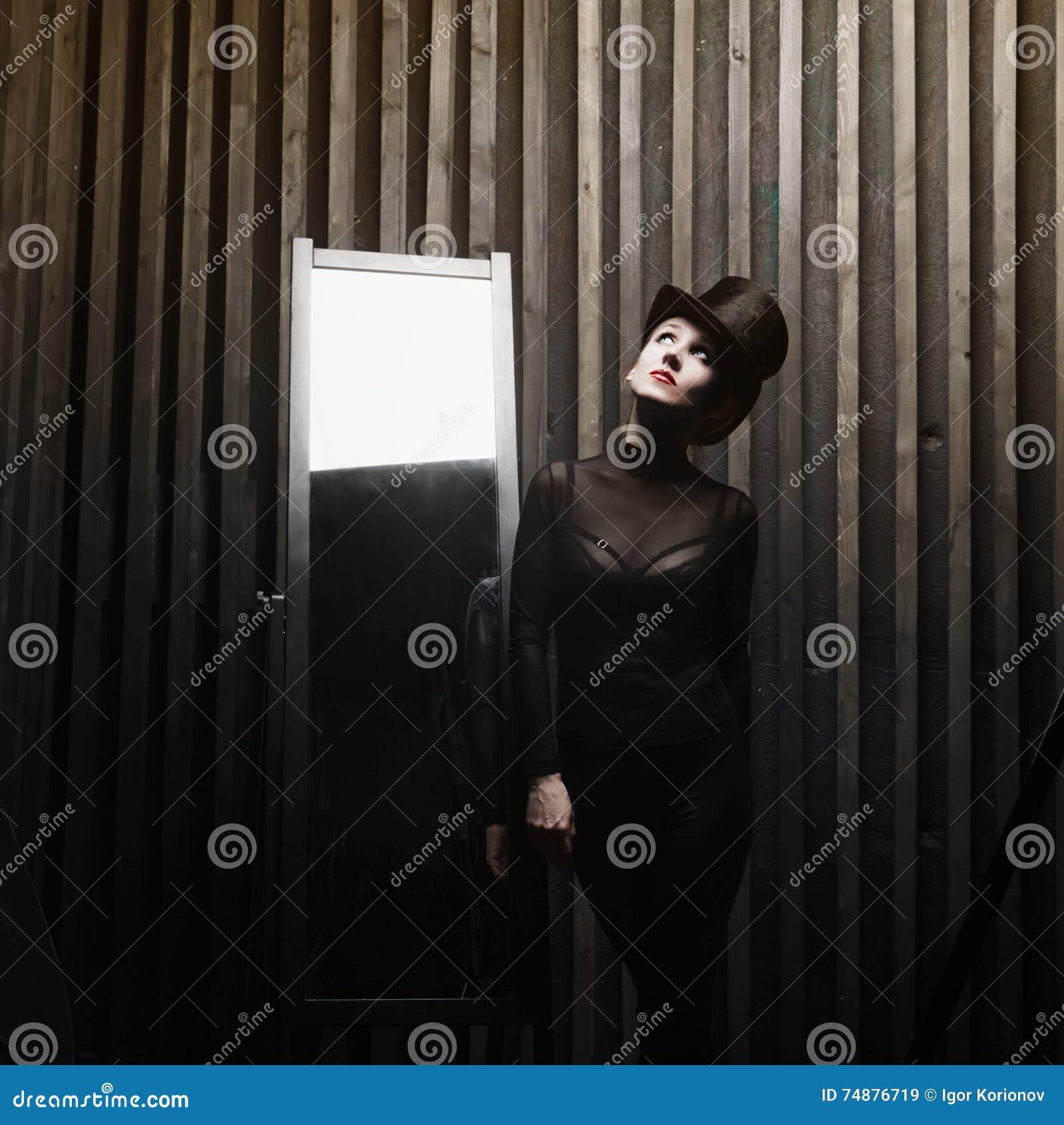 Mulher que veste um chapéu alto perto do espelho