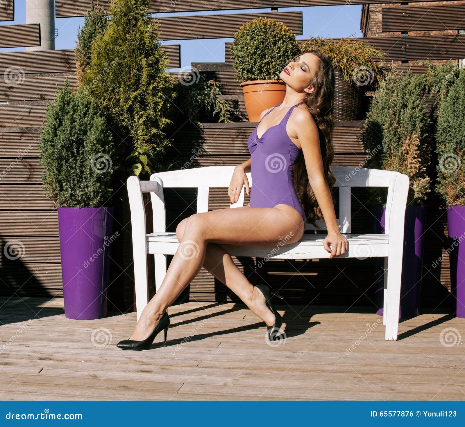 A mulher real nova da beleza após termas no biquini e a veste no hotel recorrem, no terraço apreciando termas mornos do sol