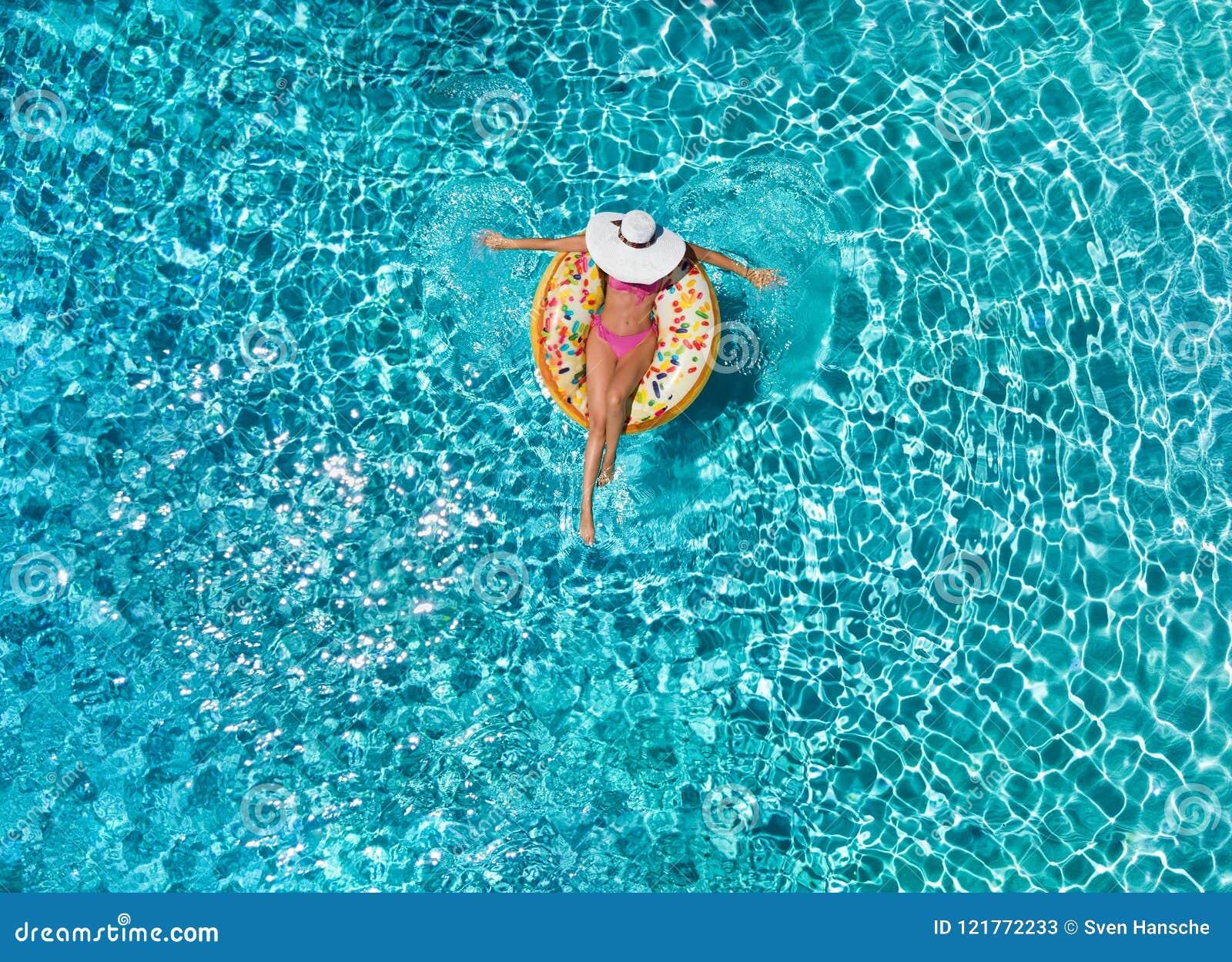 A mulher relaxa em um flutuador em forma de anel sobre a água azul, efervescente da associação
