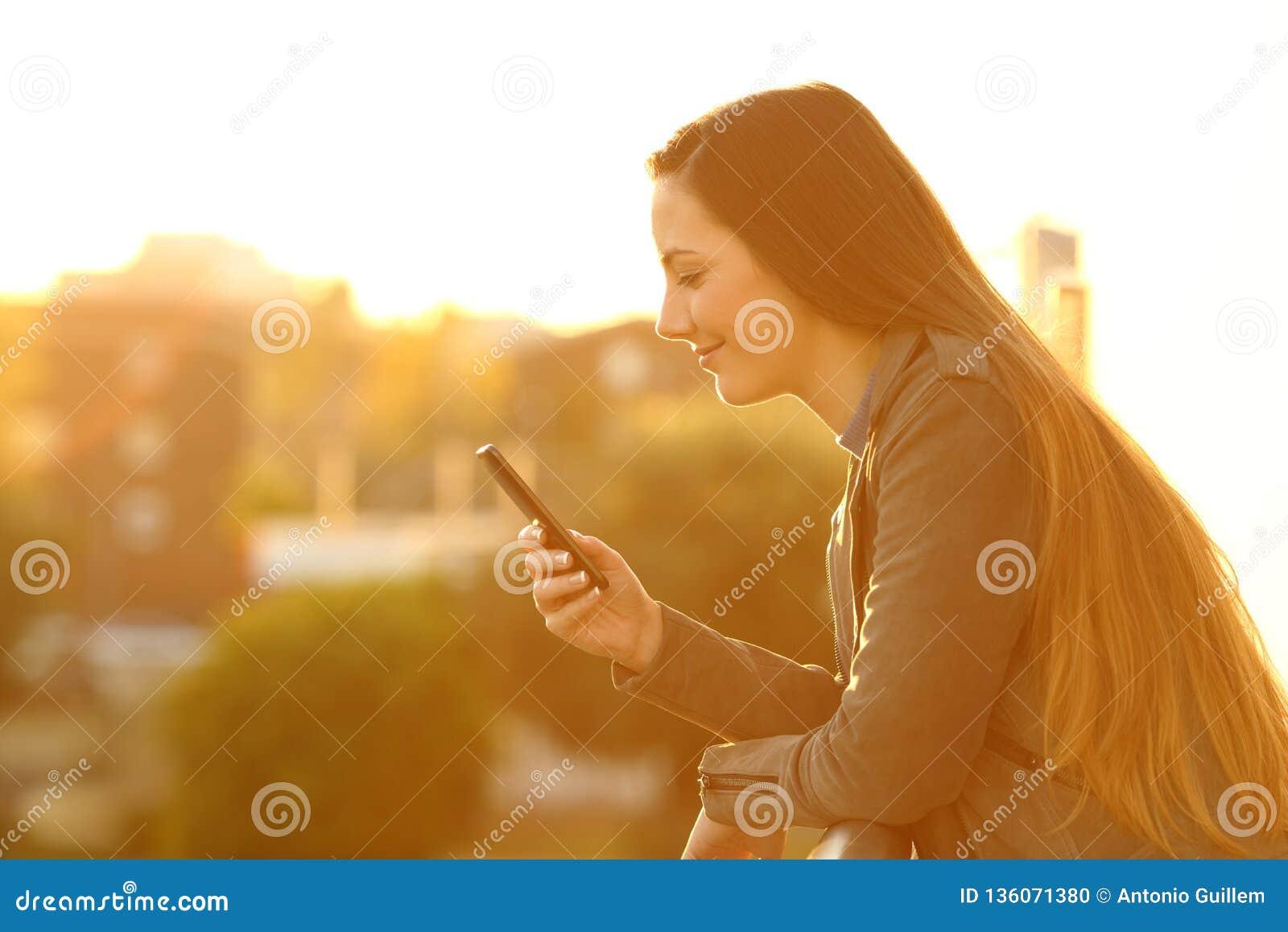 Mulher relaxado em um balcão que verifica o telefone esperto