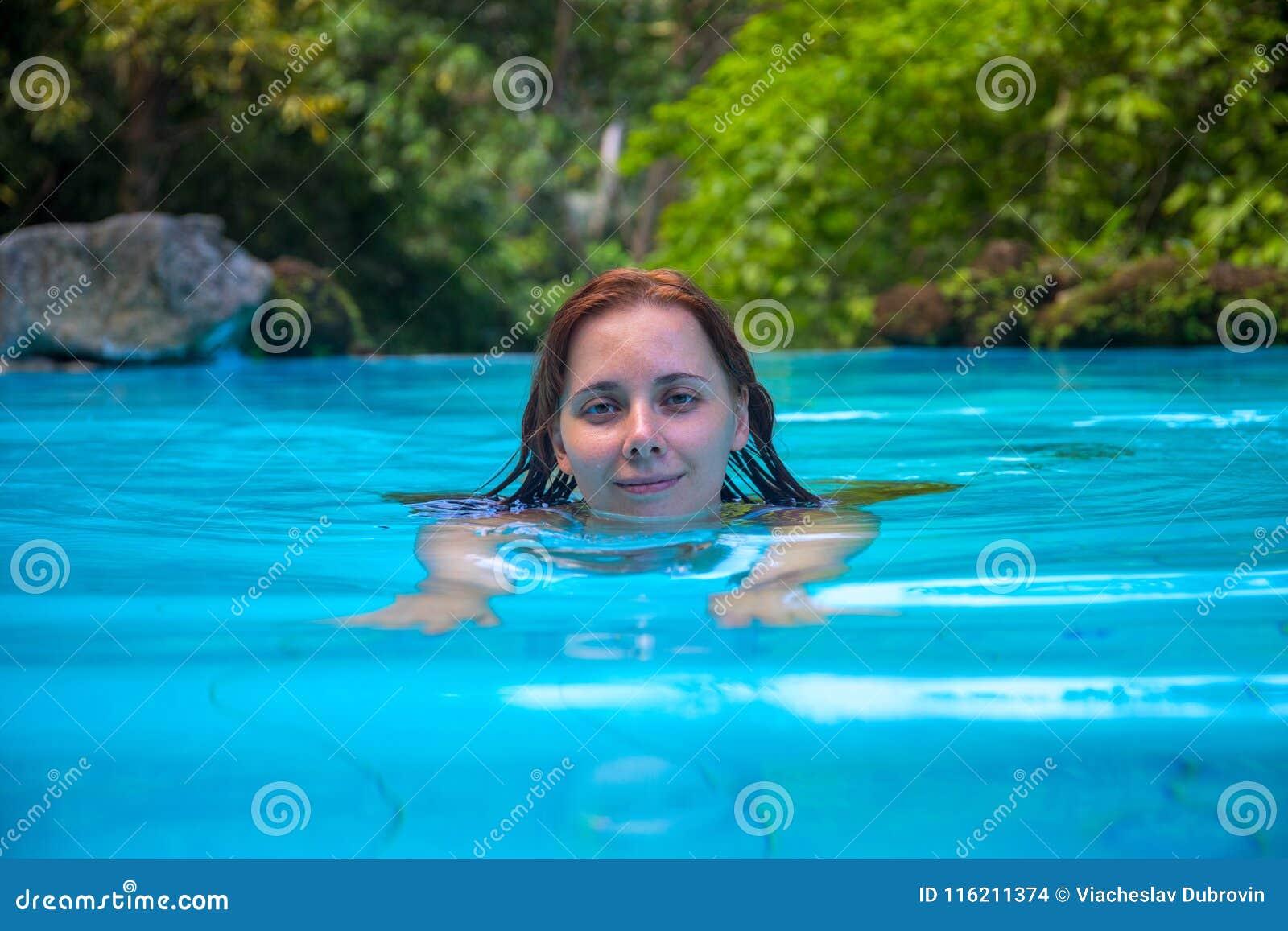 4a0b46914 Mulher relaxado na piscina aberta Menina da natação que olha in camera  Menina na piscina aberta Foto da experiência das férias de verão Cena  tropical do ...