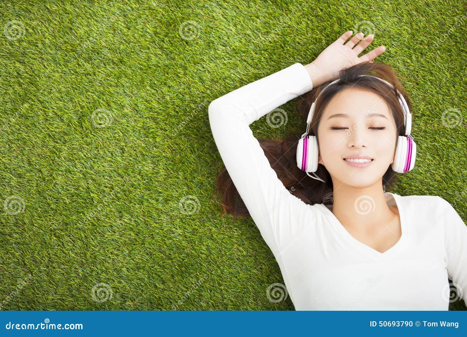 Mulher relaxado que escuta a música com fones de ouvido