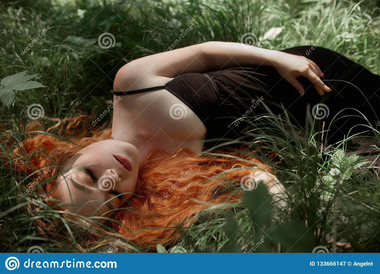 Mulher romântica com o cabelo vermelho que encontra-se na grama nas madeiras Uma menina em sonos pretos claros e em sonhos de um