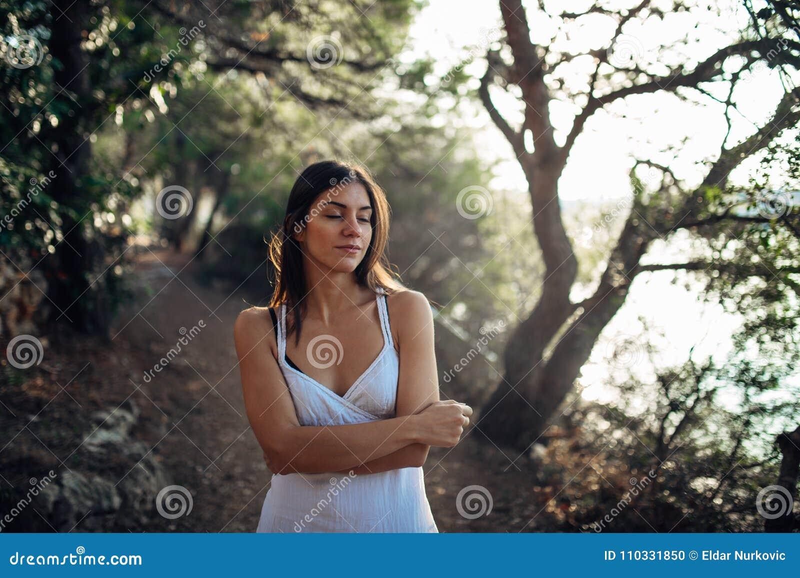 Mulher romântica que aprecia a caminhada na natureza em uma manhã ensolarada A fêmea despreocupada consciente no esforço do senti