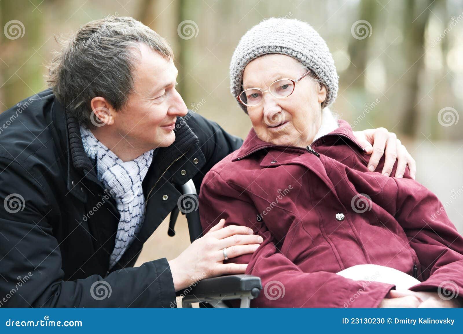 Mulher sênior idosa na cadeira de rodas com filho cuidadoso