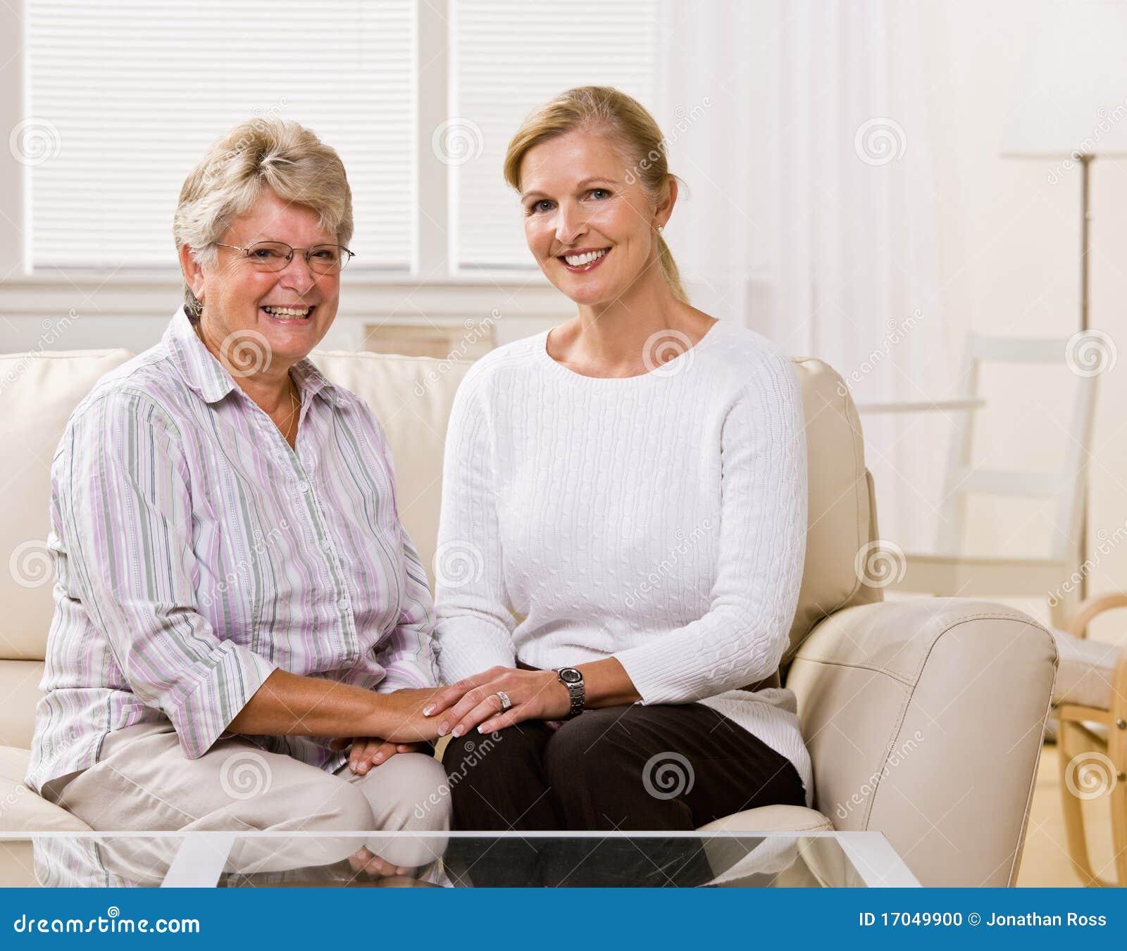 Mulher sênior que senta-se com a filha na sala de visitas