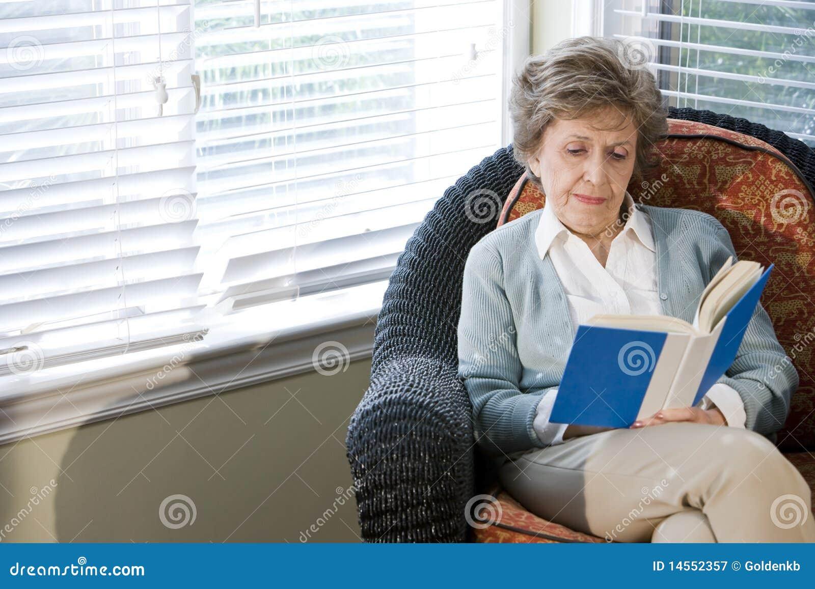 Mulher sênior que senta-se na leitura da cadeira da sala de visitas