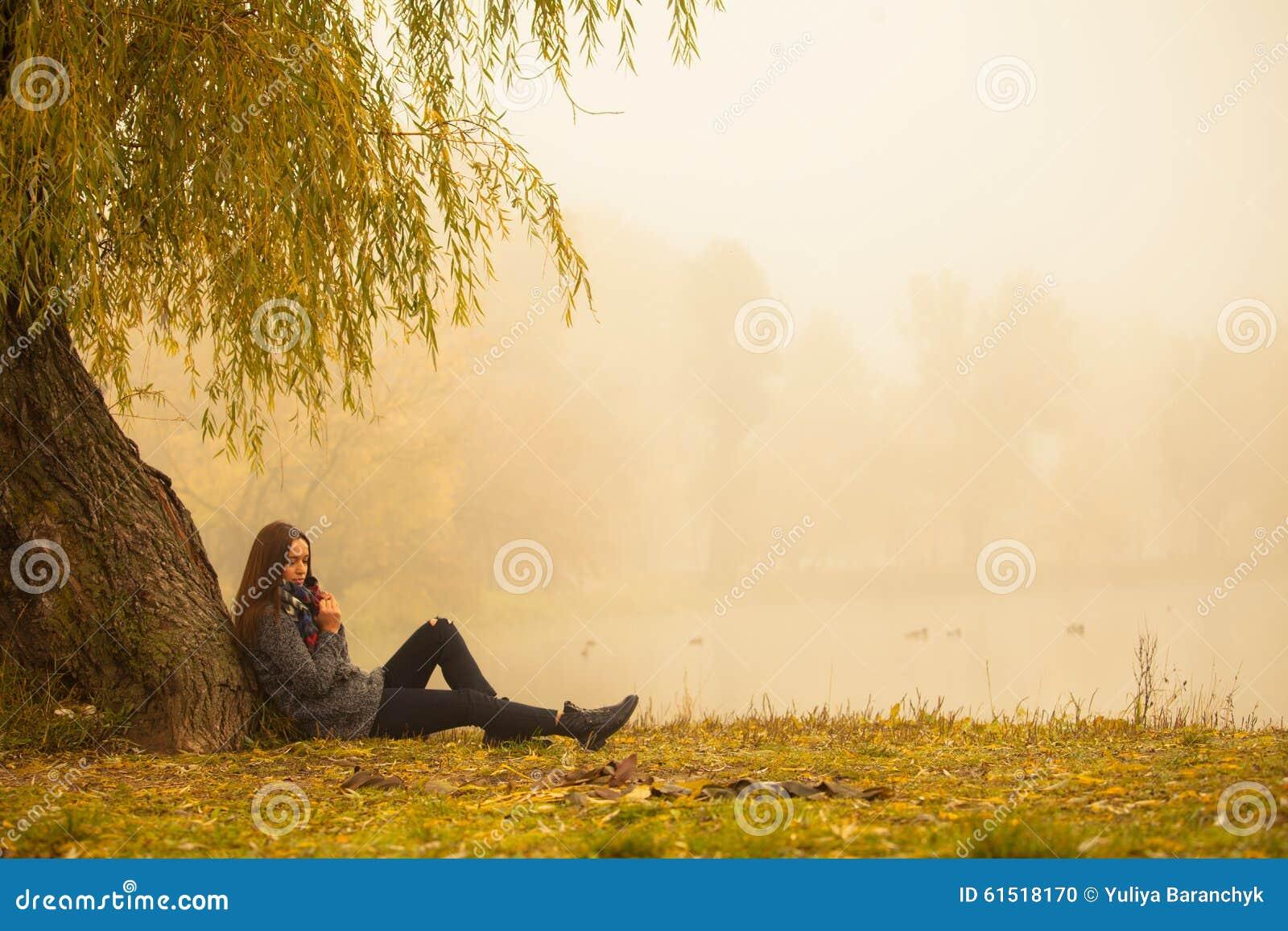 Mulher só que tem o resto sob a árvore perto da água em um dia nevoento do outono
