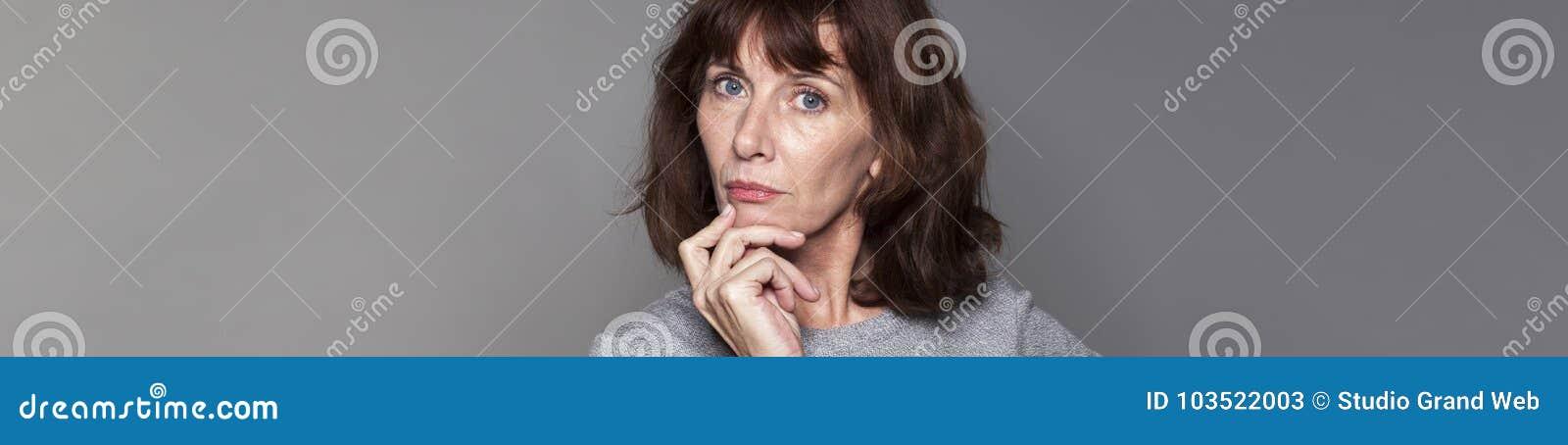 Mulher 50s bonita imaginativa que olha séria