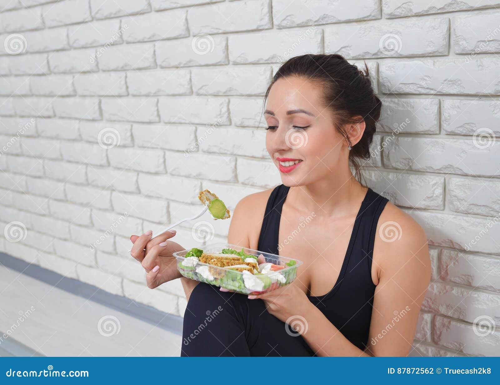 Mulher saudável apta no sportswear que come uma salada fresca após o exercício da aptidão