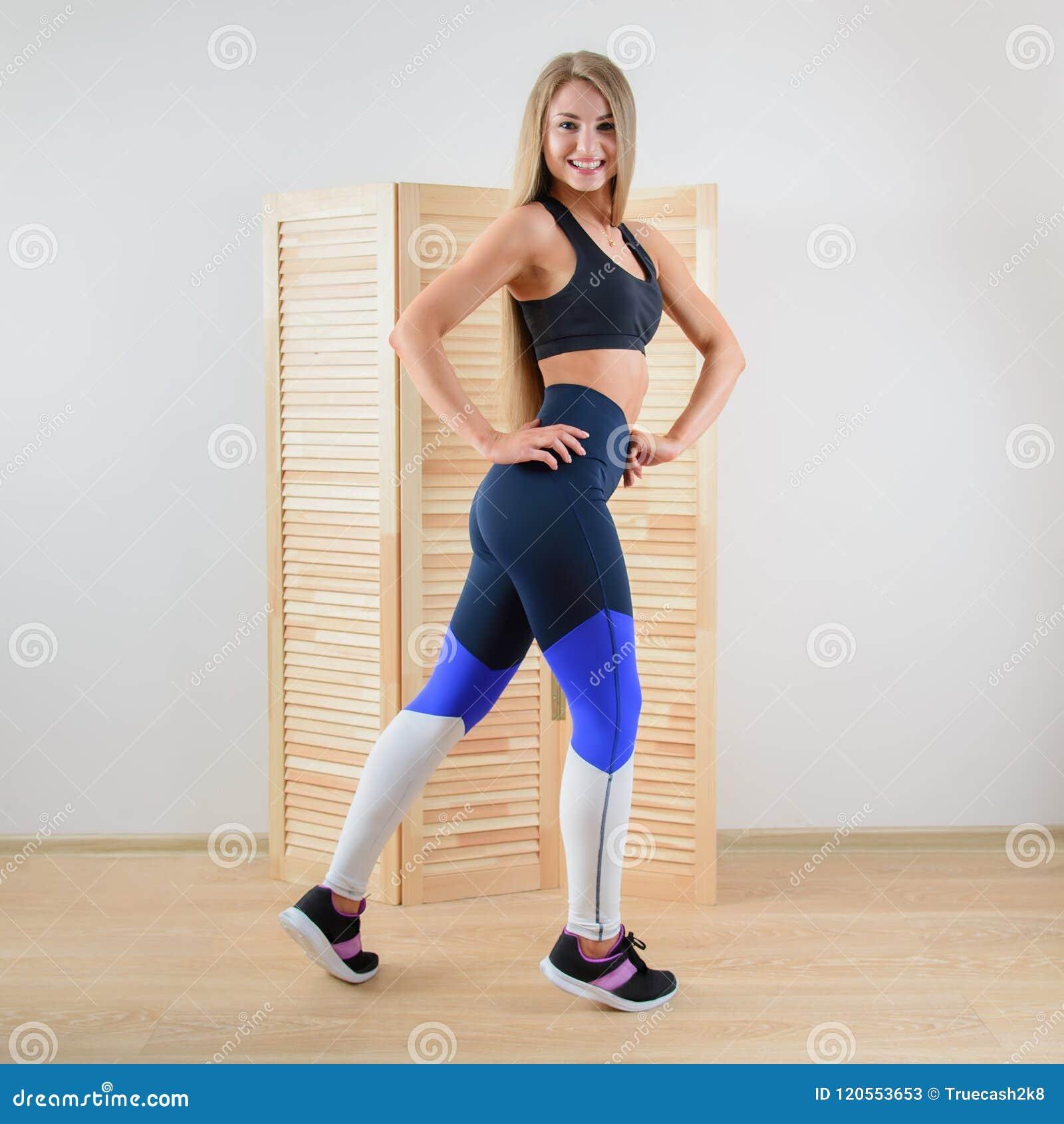 Mulher saudável nova no levantamento do sportswear Menina bonita feliz que sorri na câmera