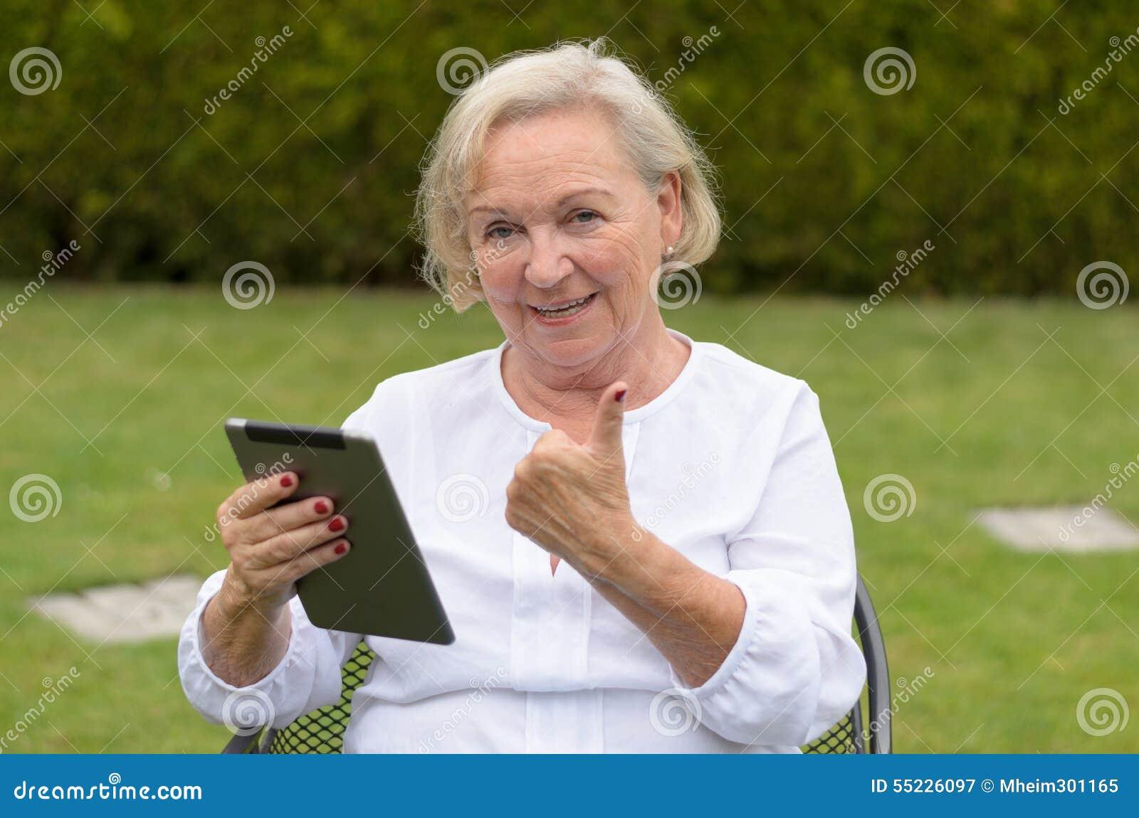 Mulher sereno superior que usa um PC preto da tabuleta