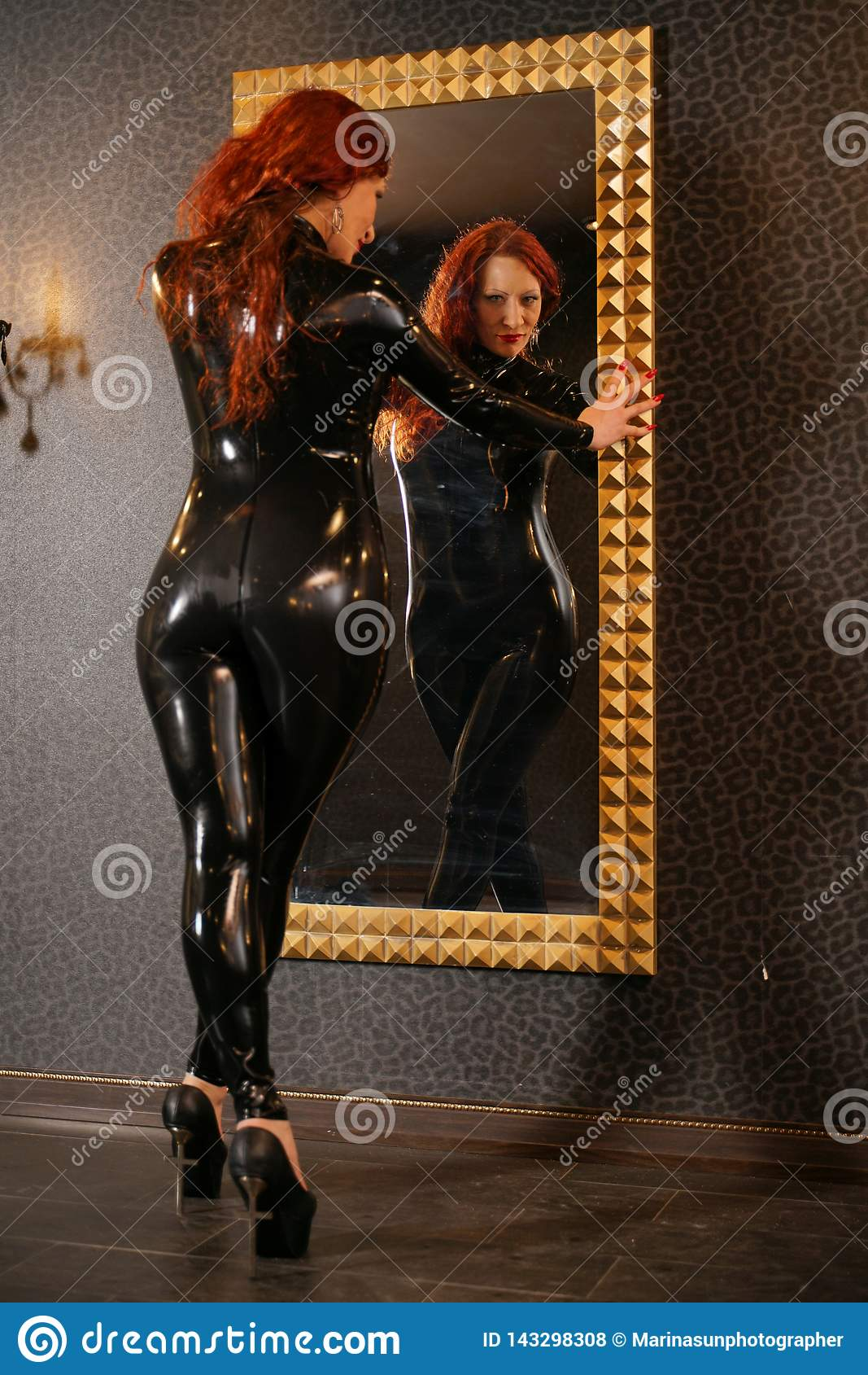 Mulher sexual do ruivo da fetiche que veste o catsuit de borracha do látex preto e que olha o espelho na sala escura