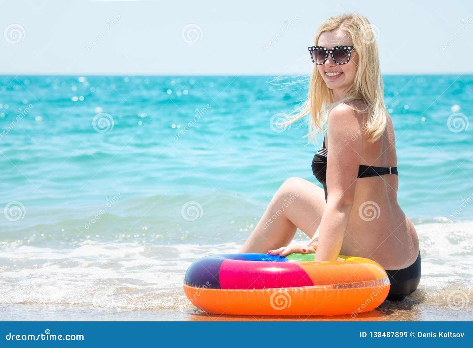 Mulher  sexy  bonita no biquini com o círculo inflável que senta-se na praia
