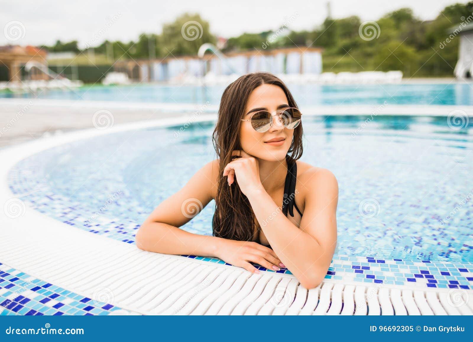 Mulher  sexy  bonita que relaxa na água da piscina que aprecia o sol do verão no dia de verão quente na borda da associação