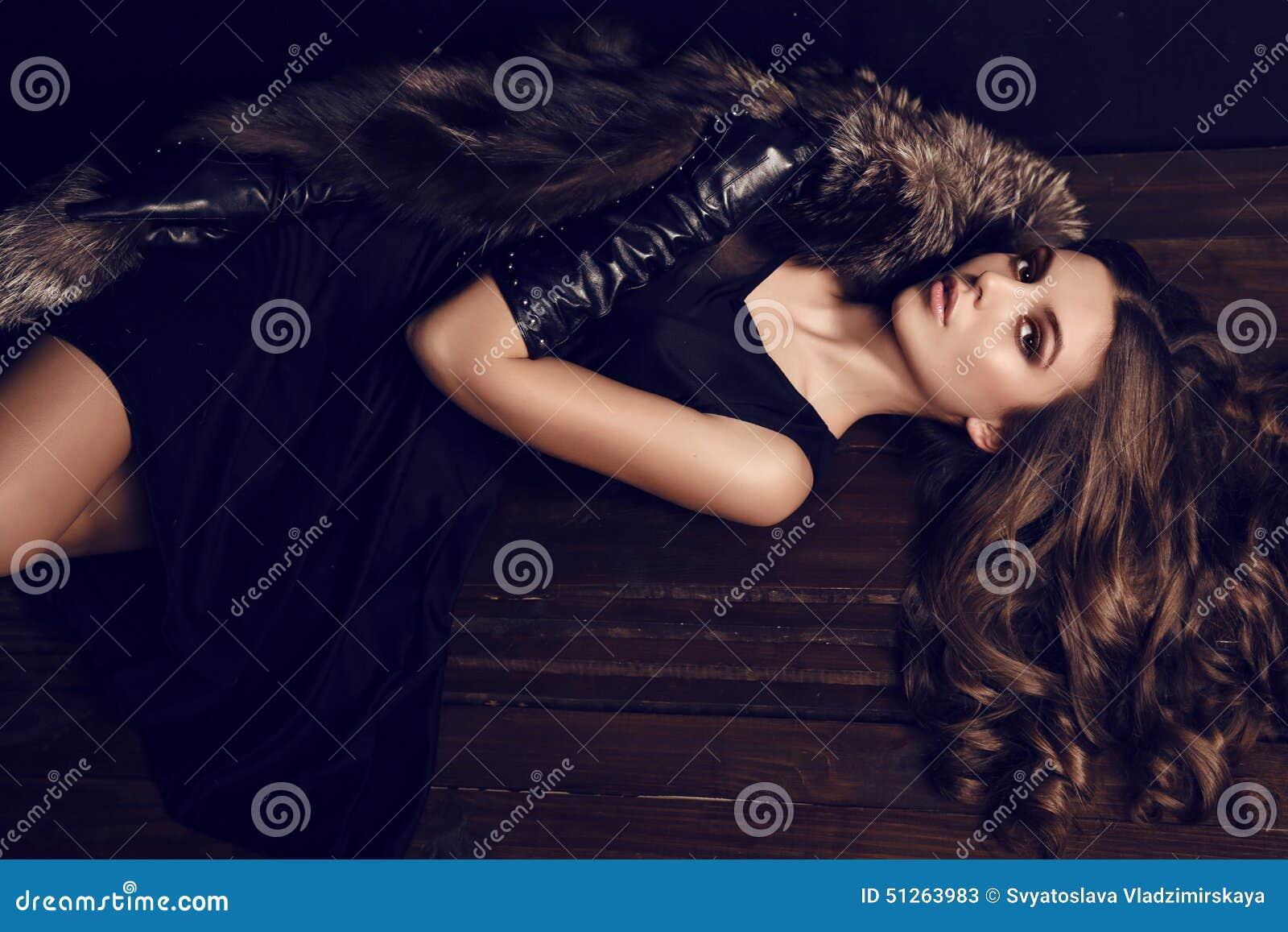 Mulher  sexy  com cabelo escuro no casaco de pele luxuoso e nas luvas de couro