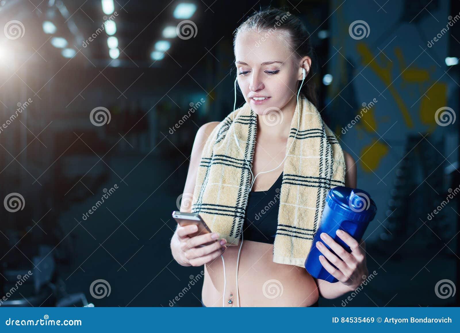 A mulher  sexy  da aptidão no sportswear que descansa após pesos exercita no gym Menina bonita com abanador e toalha