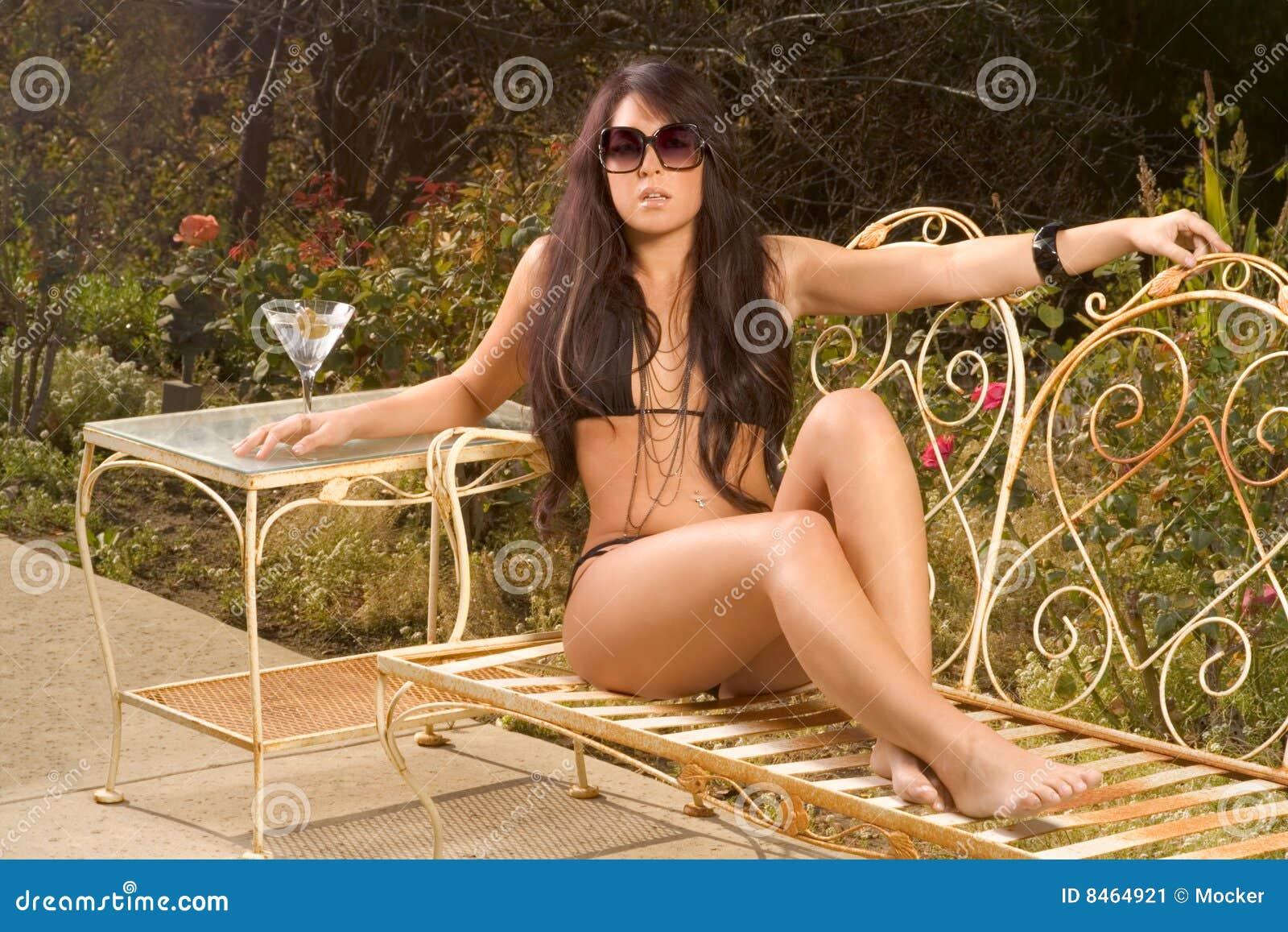 b4b5675f5 Mulher sensual nova no biquini preto que senta-se no banco do jardim do  ferro que sunbathing ao ar livre