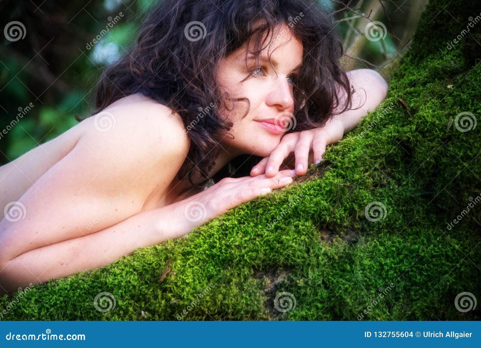 A mulher  sexy  nova de cabelo escuro está encontrando-se felizmente satisfeitamente em uma árvore de salgueiro velha no musgo ve
