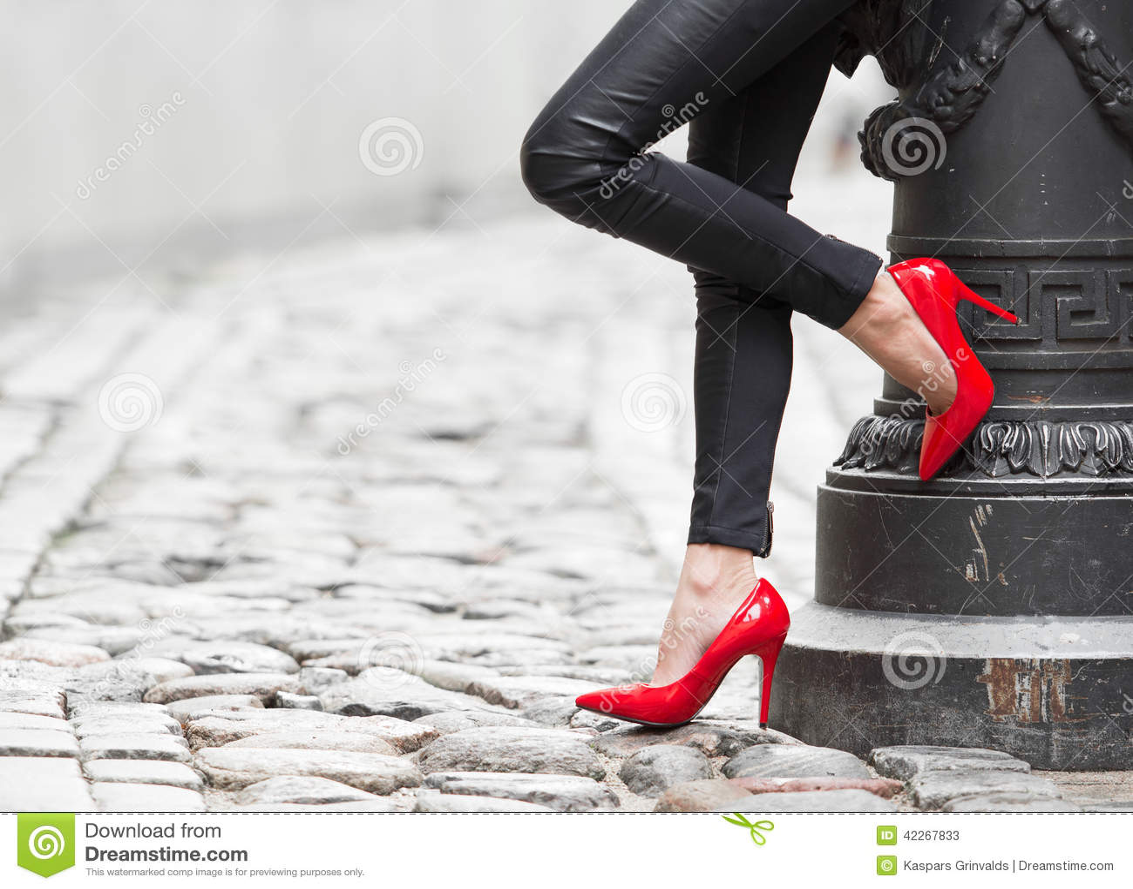 Mulher  sexy  que veste sapatas vermelhas do salto alto na cidade