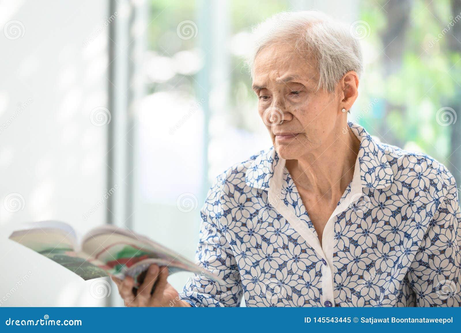 A mulher superior asi?tica que l? um livro relaxado em casa, mulher idosa gasta seu livro de leitura do tempo livre