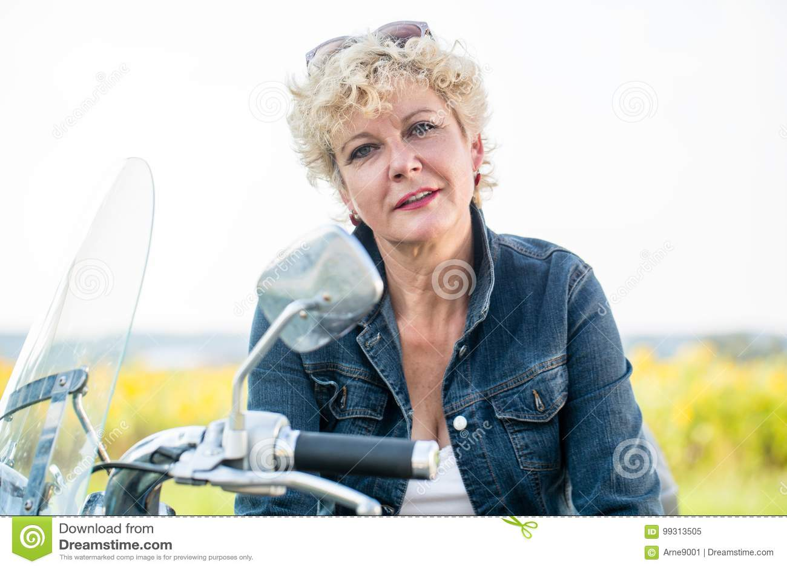 Mulher superior ativa que veste um revestimento azul da sarja de Nimes ao sentar-se sobre