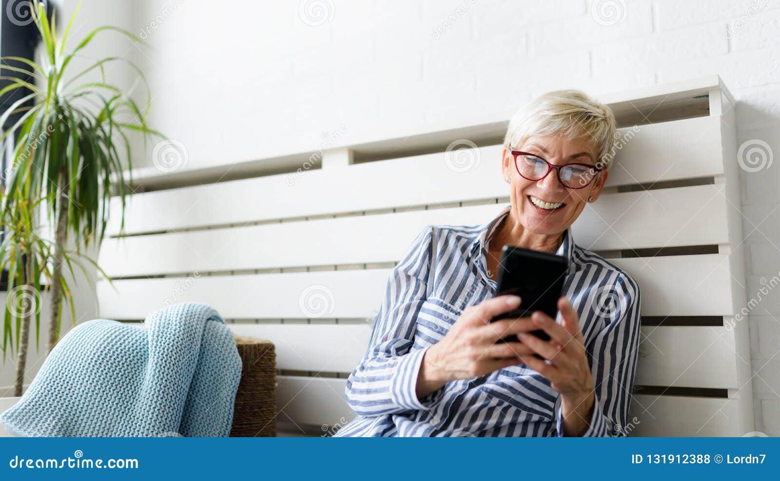 Mulher superior bonita de sorriso que usa a tabuleta digital em casa