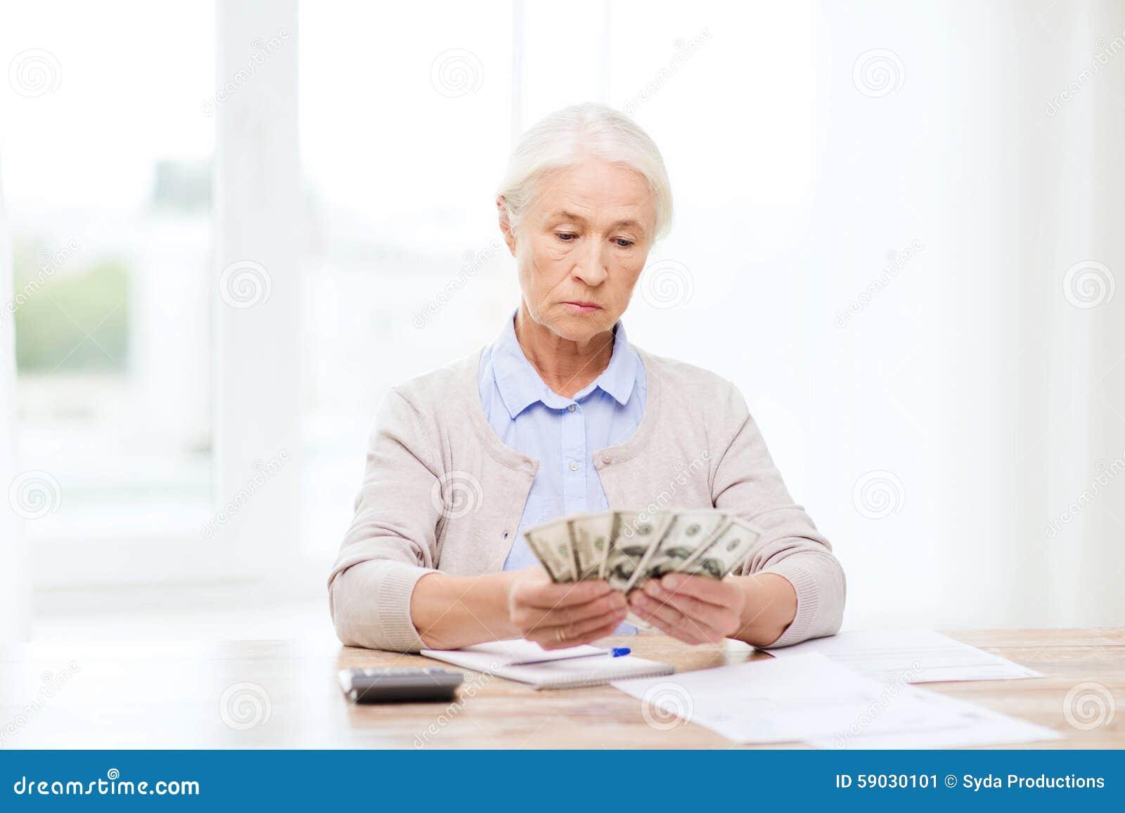 Mulher superior com dinheiro e papéis em casa