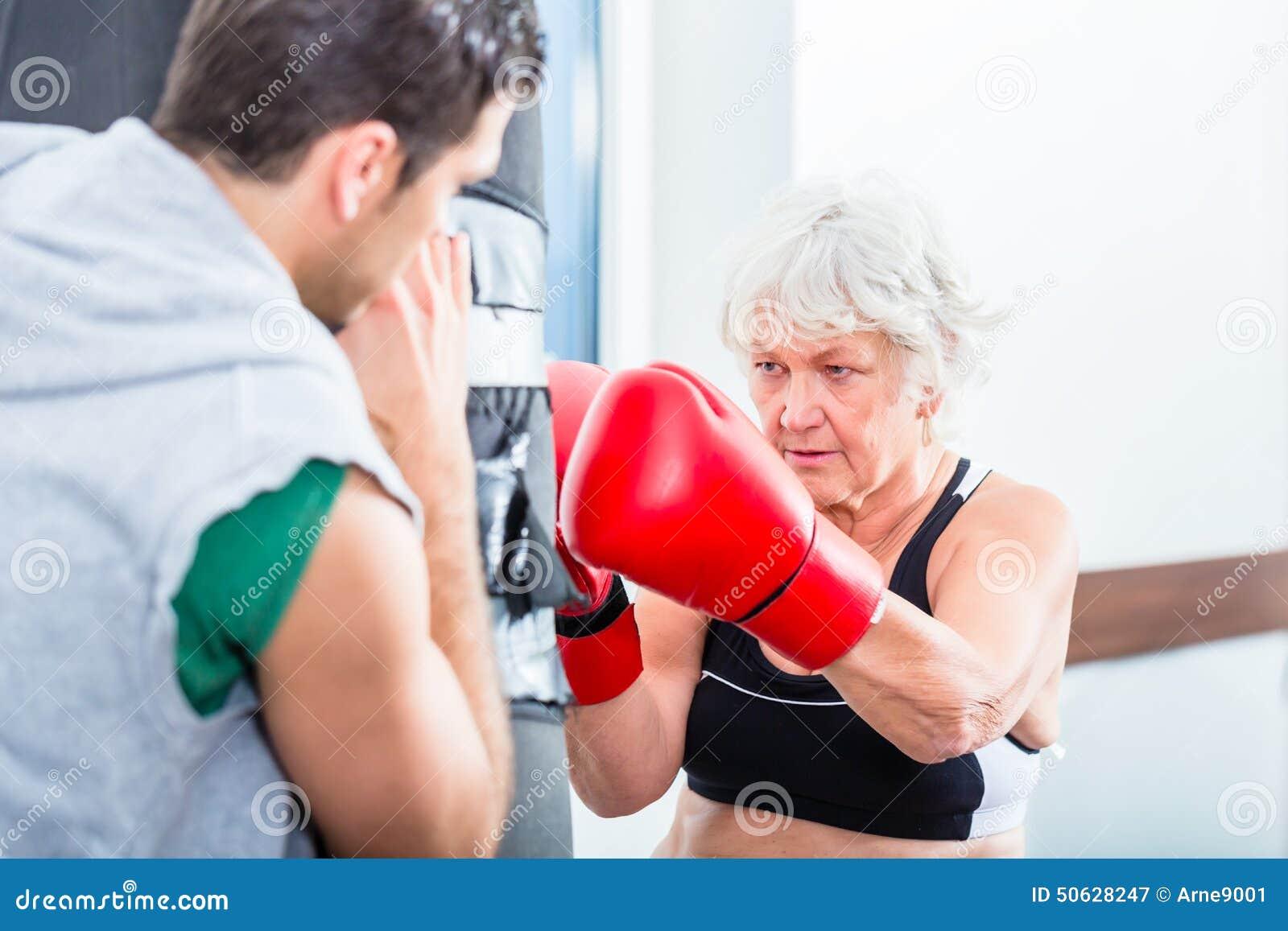 Mulher superior com o instrutor no boxe de treino do encaixotamento
