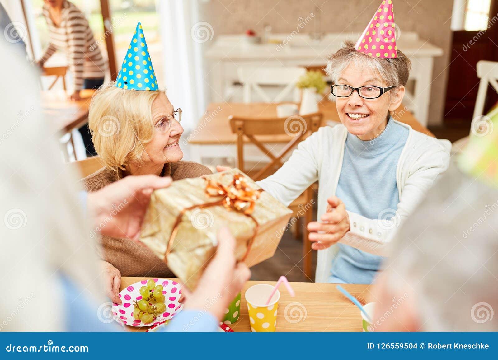 A mulher superior como uma menina do aniversário está feliz
