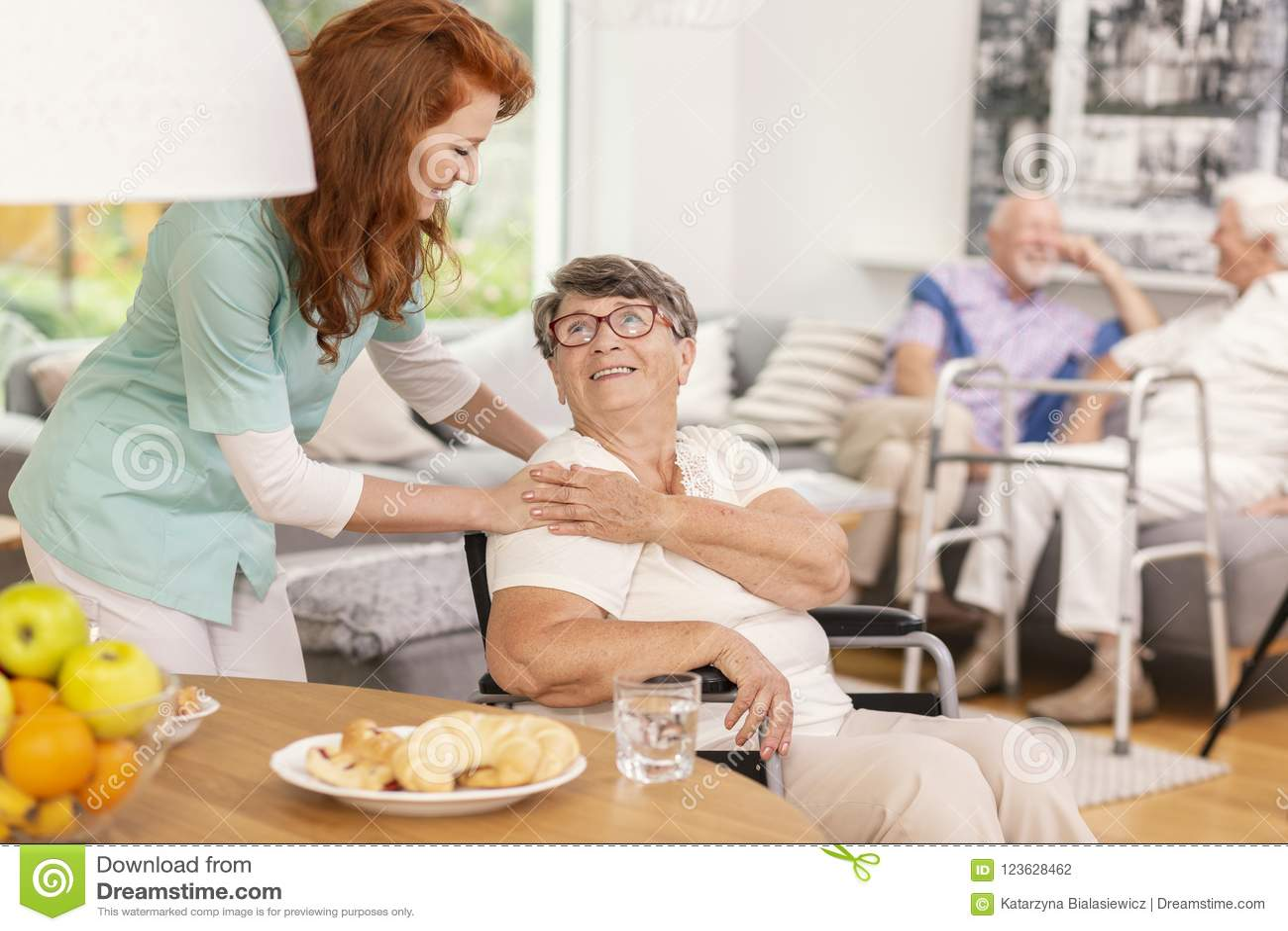 Mulher superior de sorriso de apoio da enfermeira amigável na casa dos cuidados