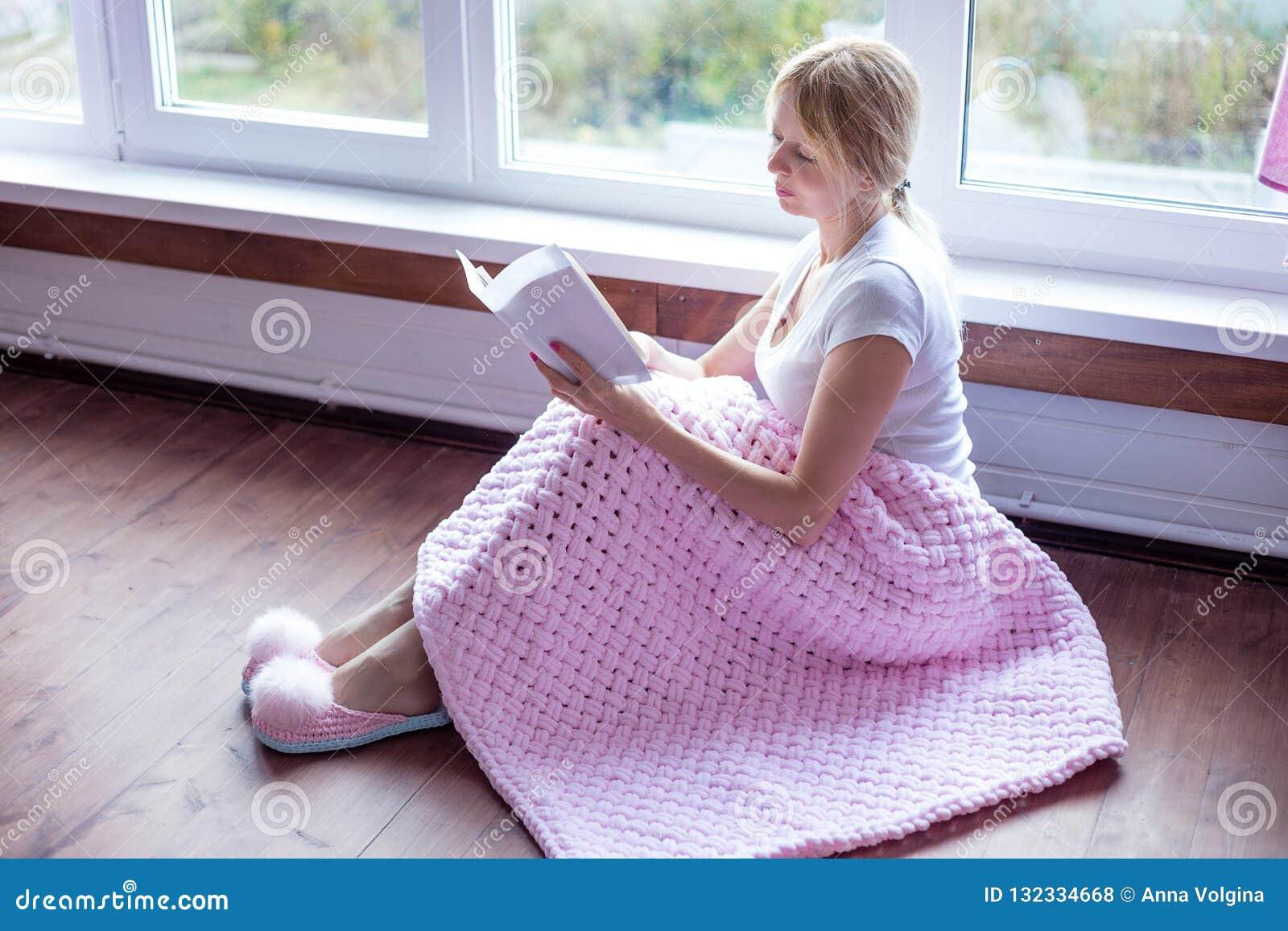 Mulher superior de sorriso que lê um livro em casa