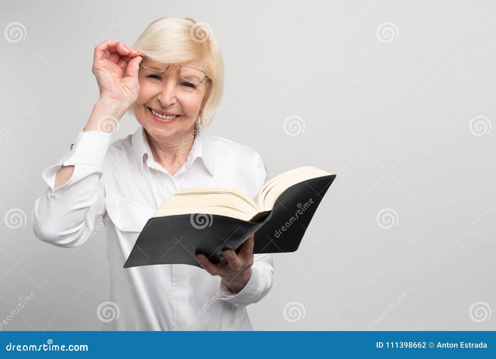 A mulher superior está estando na sala e está lendo um livro Está tentando aprender o somethinf novo na aposentadoria porque