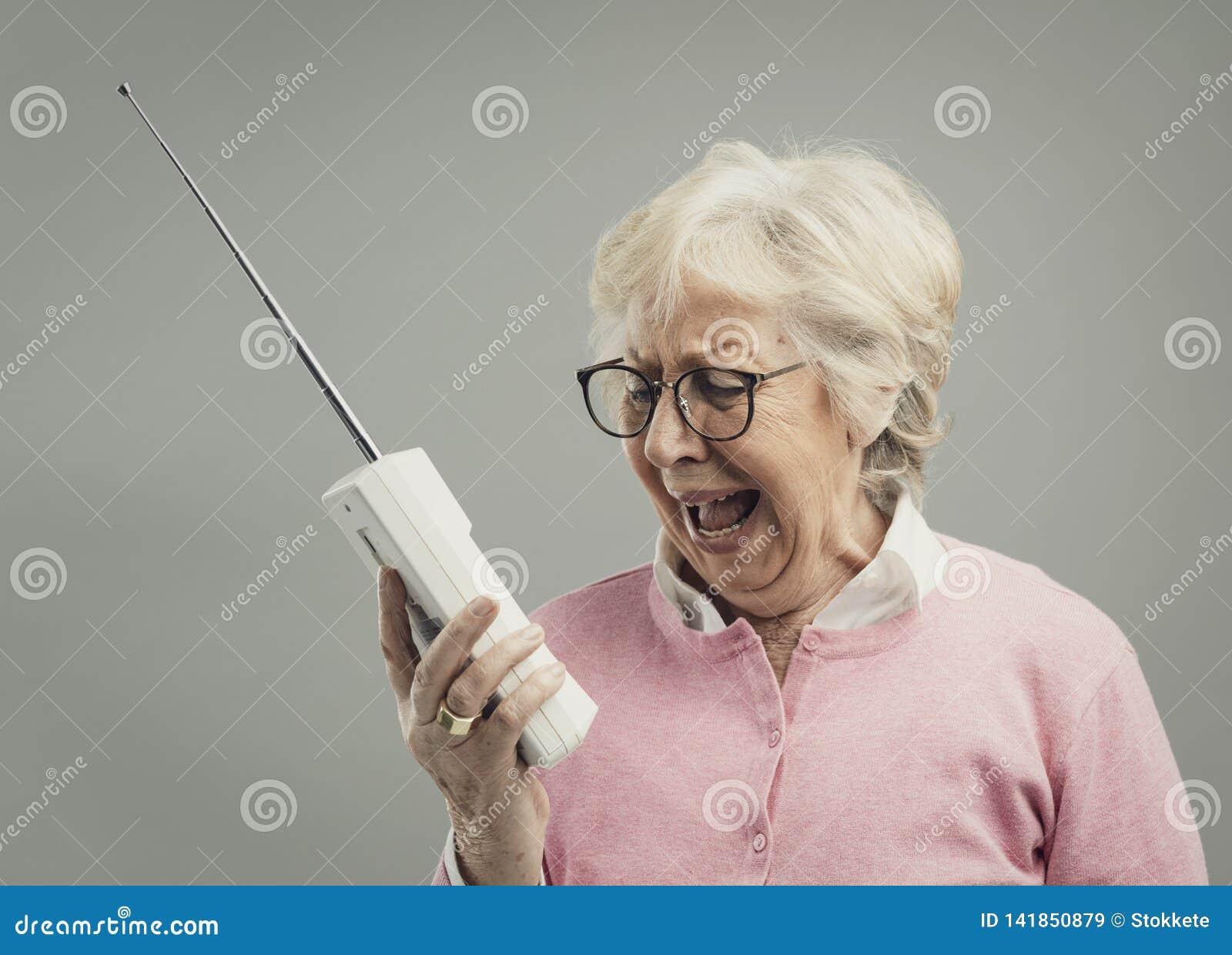 Mulher superior frustrante que usa um telefone velho