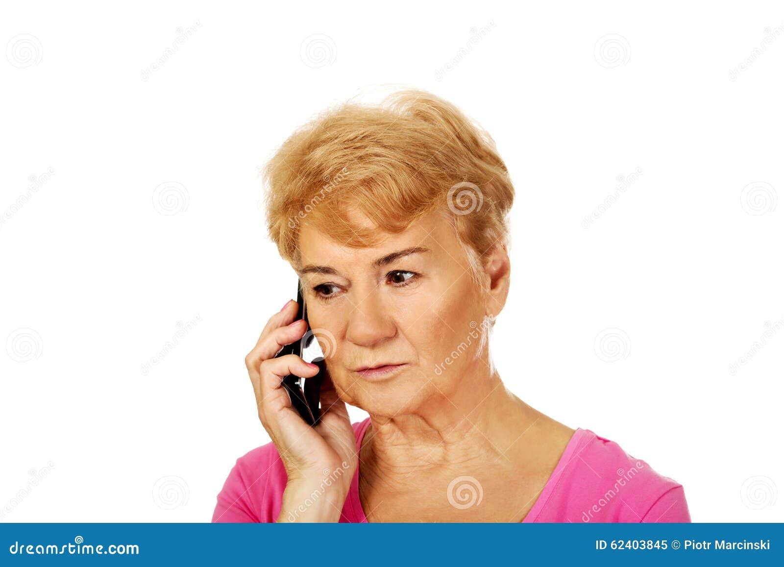 Mulher superior preocupada que fala através do telefone