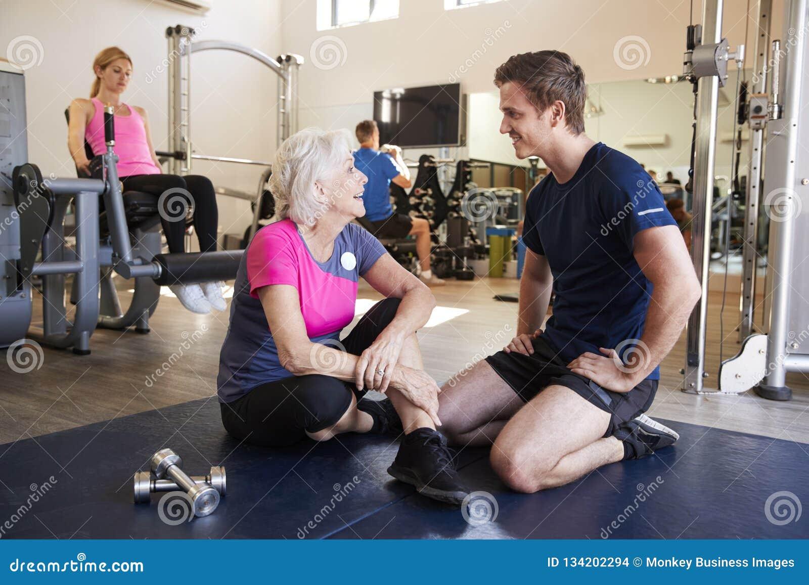 Mulher superior que discute o programa do exercício com o instrutor pessoal masculino In Gym