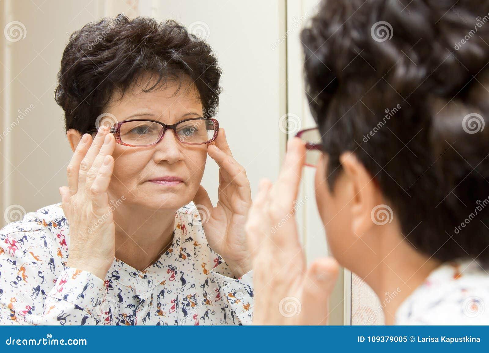 Mulher superior que tenta em vidros novos e que olha no espelho