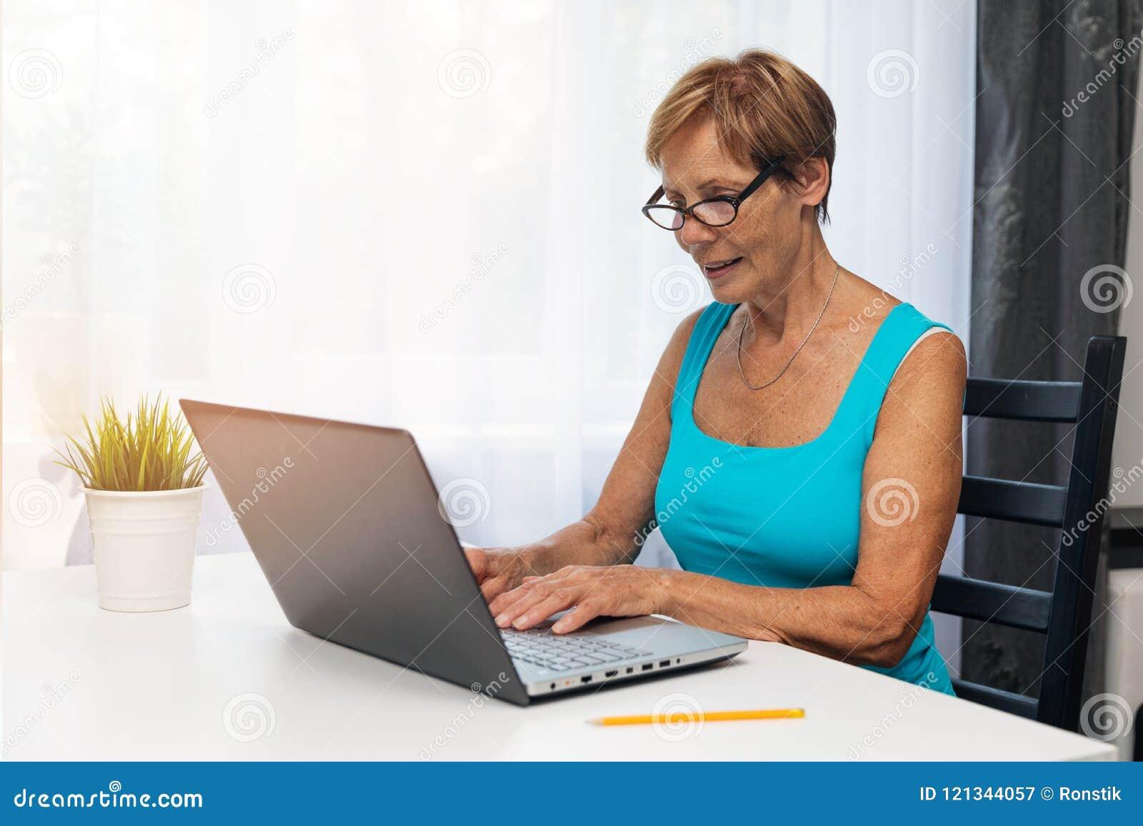 Mulher superior que usa o laptop em casa